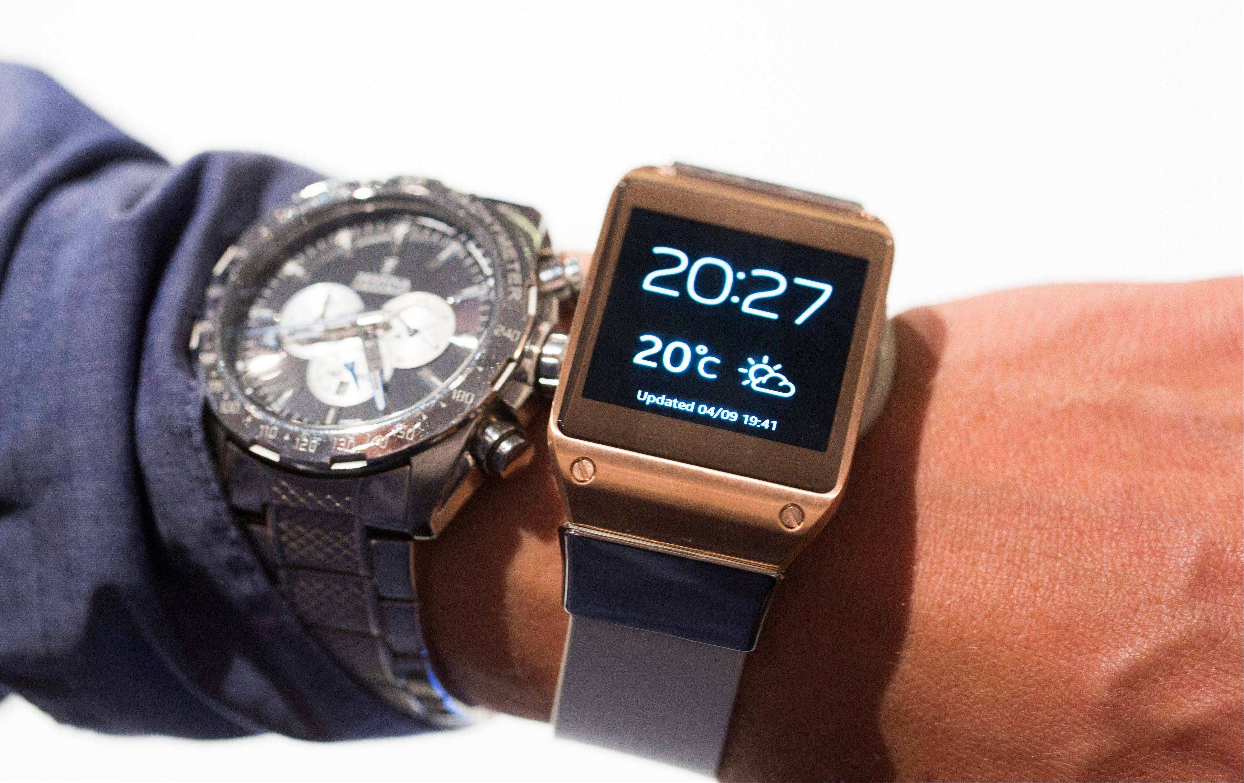 A man tries a Samsung Galaxy Gear, right, next to his regular watch Wednesday after the presentation in Berlin, Germany. Samsung has unveiled a highly anticipated digital wristwatch well ahead of a similar product expected from rival Apple. The so-called smartwatch is what some technology analysts believe could become this year's must-have holiday gift. Samsung unveiled the Galaxy Gear on Wednesday in Berlin ahead of the annual IFA consumer electronics show.