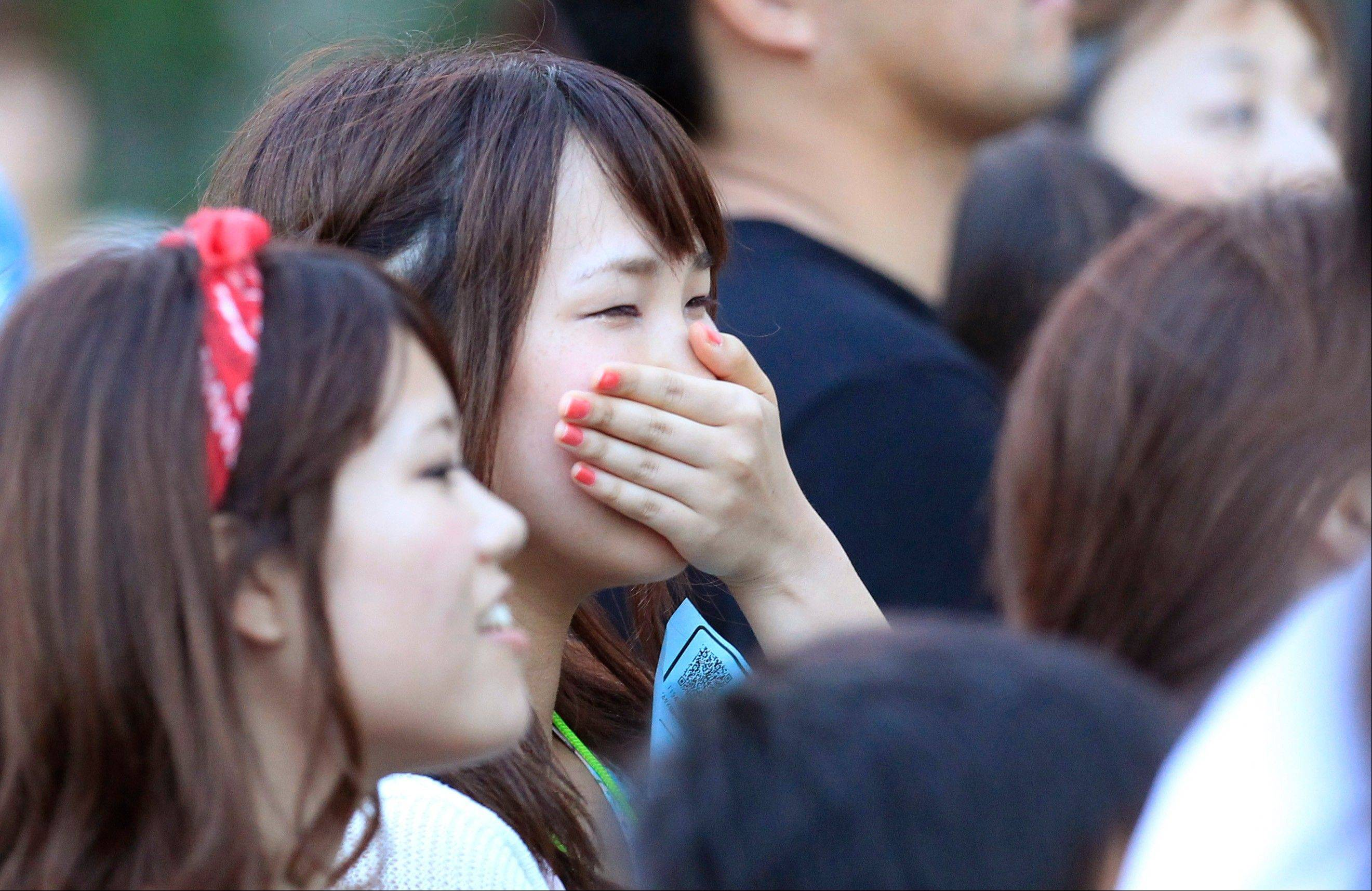 A woman is brought to tears listening to Chris Hart sing at an outdoor concert in Tokyo.