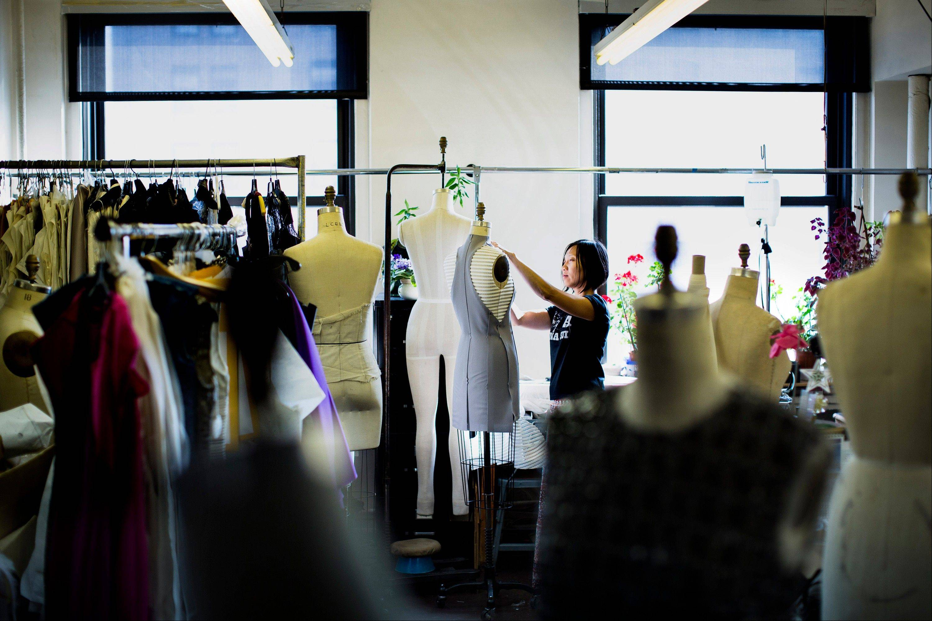 Designer Annie Le handles a dress on a mannequin in the production room of the New York studio of fashion designer Carmen Marc Valvo, as he and his staff create his Spring 2014 collection for a Fashion Week runway show.