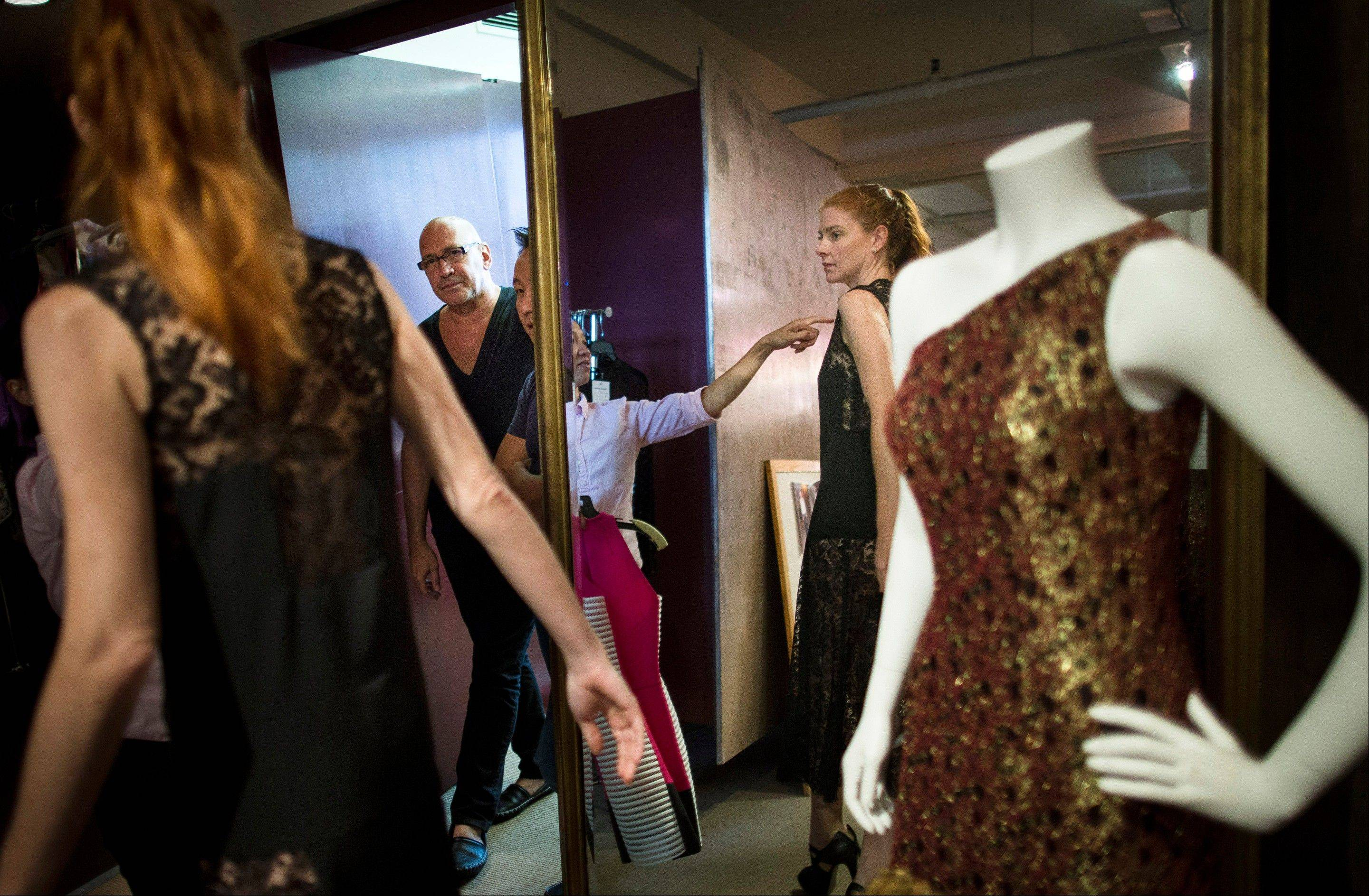 Fashion designer Carmen Marc Valvo, in glasses, watches his muse-model Taylor Foster be fitted for a dress at Valvo's New York studio.