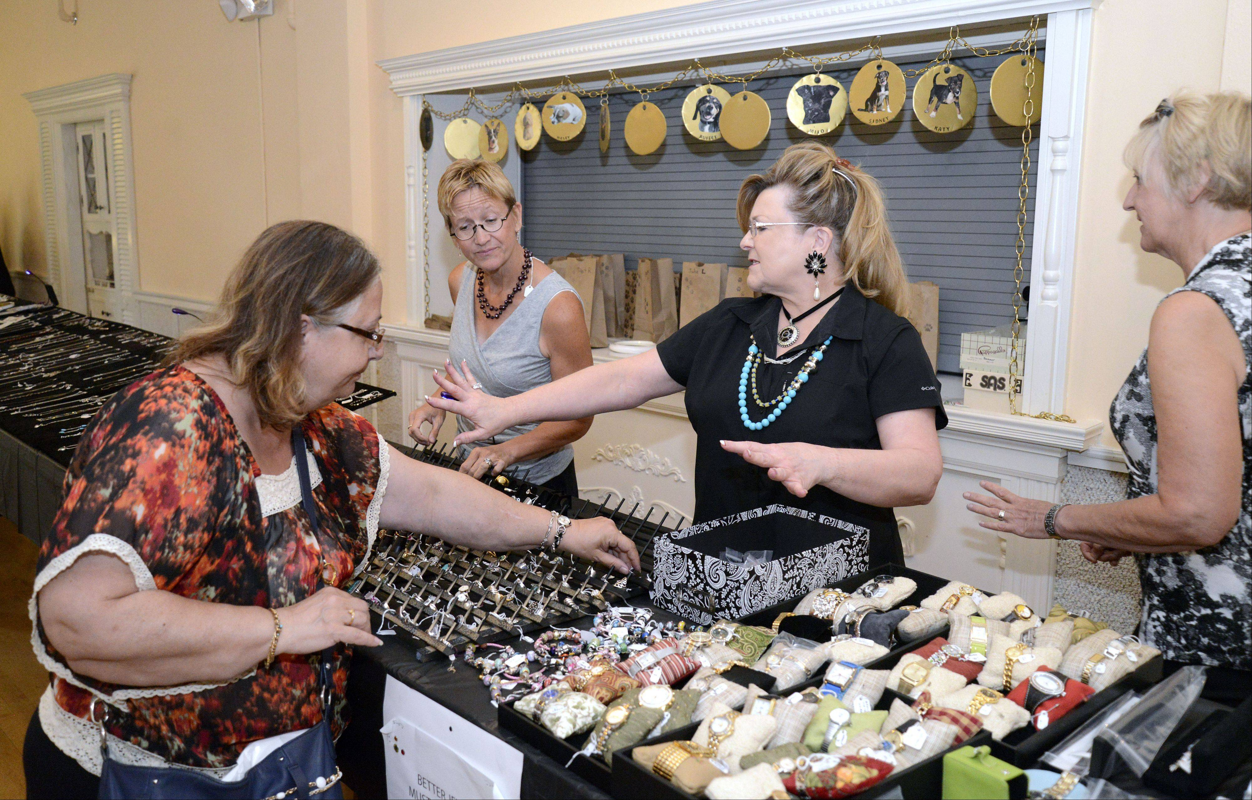 Linda Anderson of Bartlett, center, shows off a ring to fellow volunteer Beth Graham of Geneva and shopper Mary Harmon of Chicago at the Jewelry Faire running in conjunction with the Festival of the Vine in Geneva on Saturday.