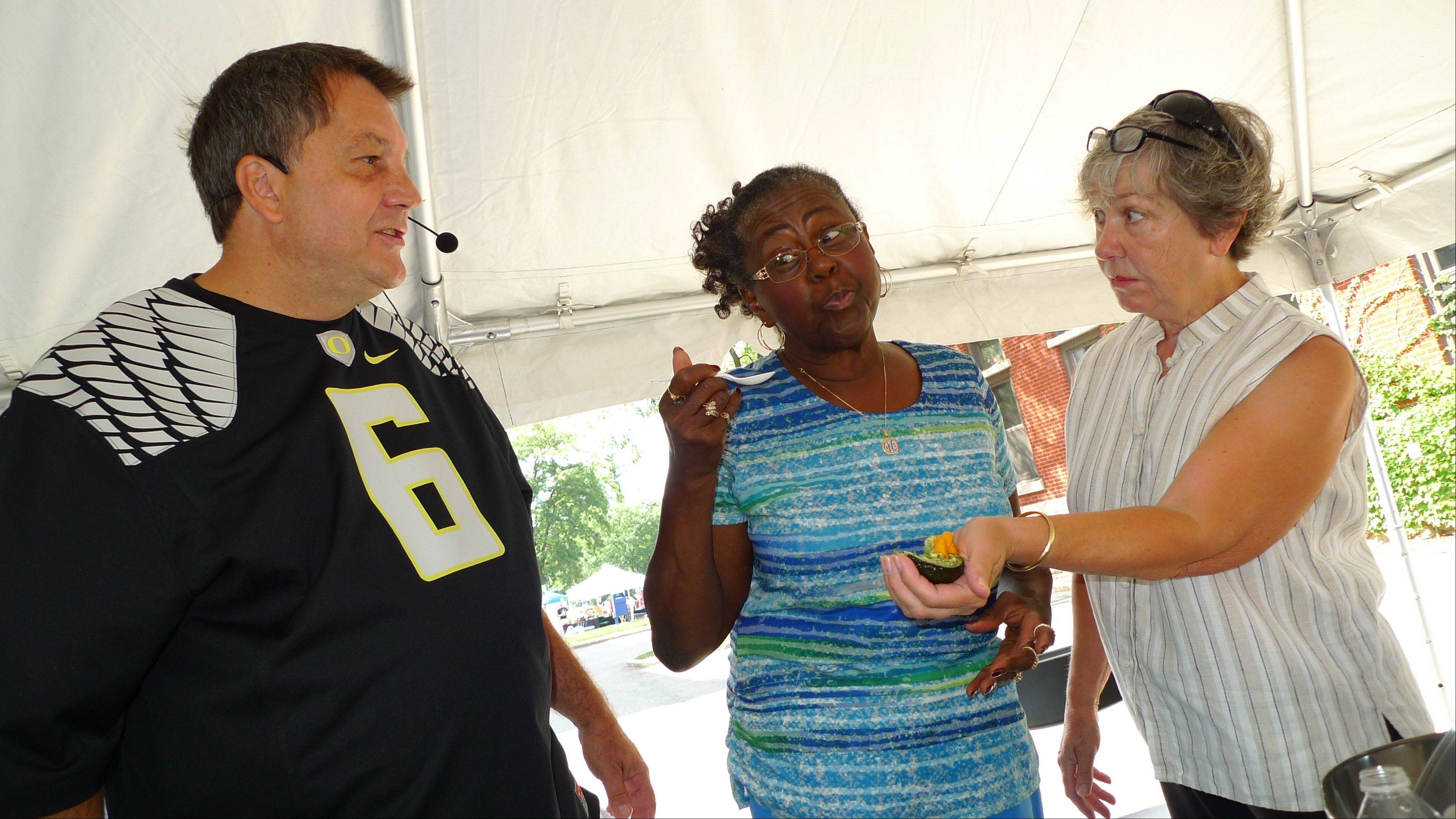 Laszlo Marton of the Galena Garlic Co. shows Edyth Cole of Springfield, center, and Barb Fritze of Geneva how to cook at the Geneva Festival of the Vine on Saturday.