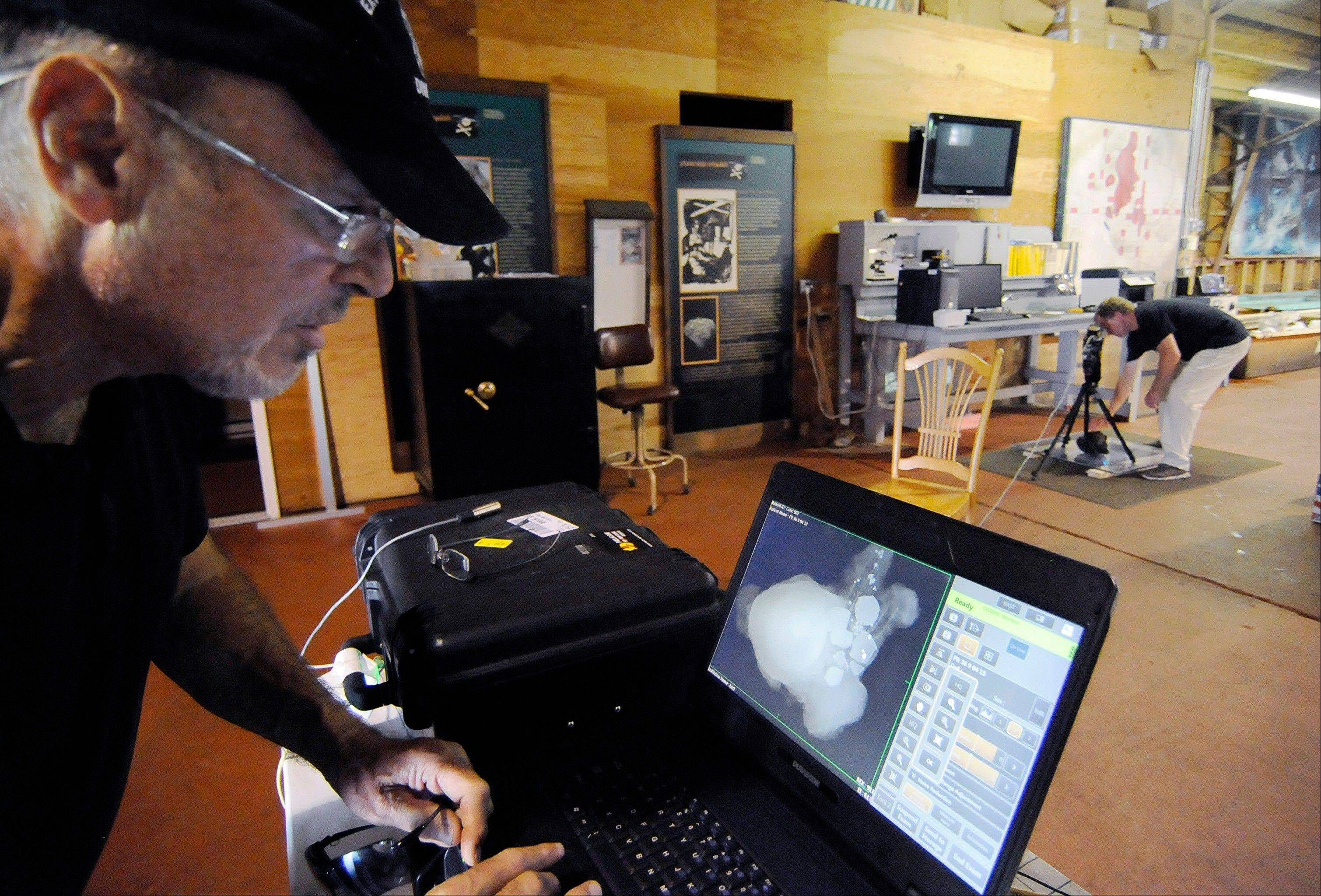 Barry Clifford, left, reviews an X-ray image of a concretion showing a cannon ball and coins that diver and conservator Chris Macort, right, had recorded in Brewster, Mass.