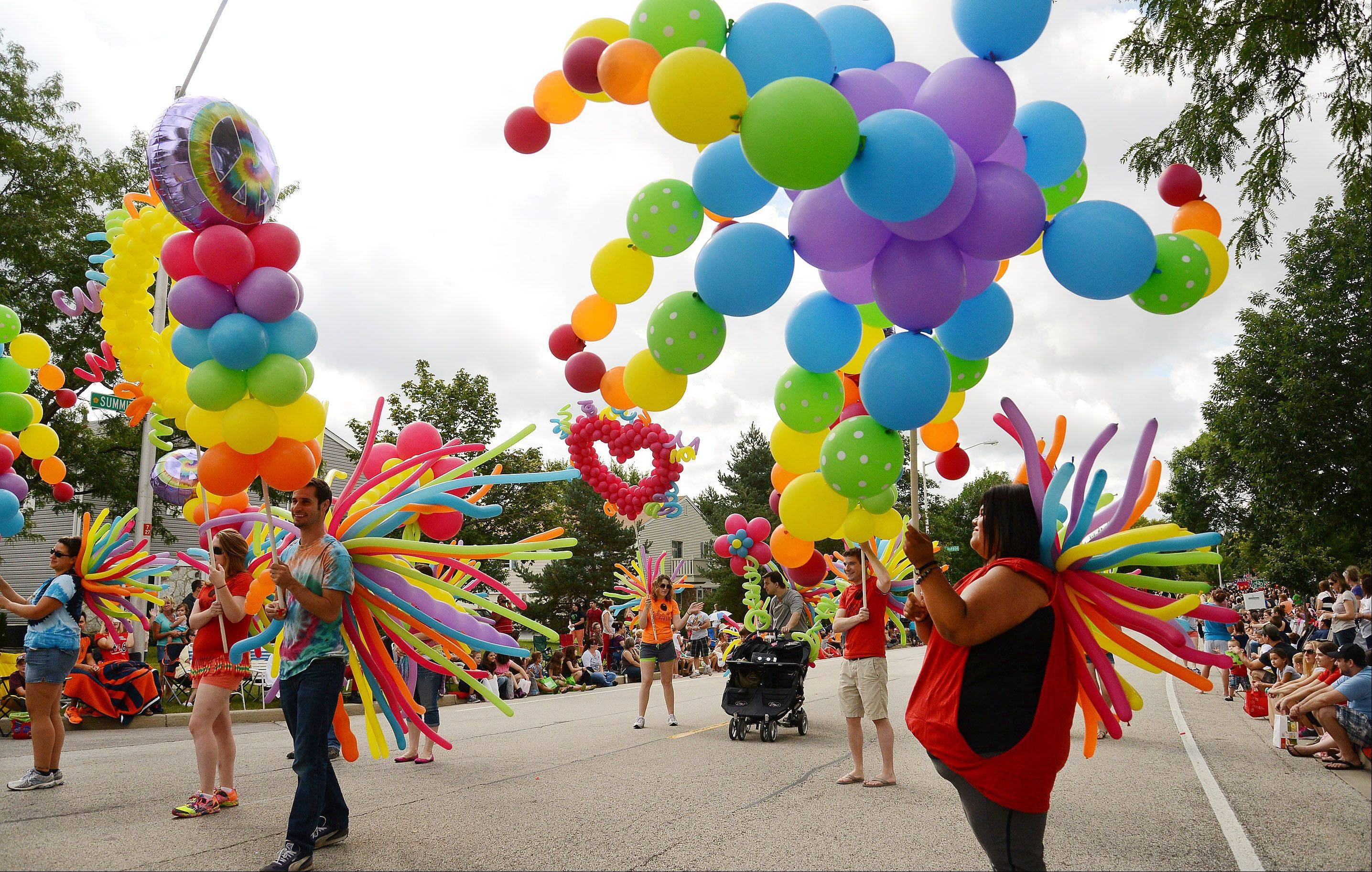 Yomara Ibarra, right, of BalloonsbyTommy.com, moves along the Septemberfest parade route with balloons on Labor Day in Schaumburg.