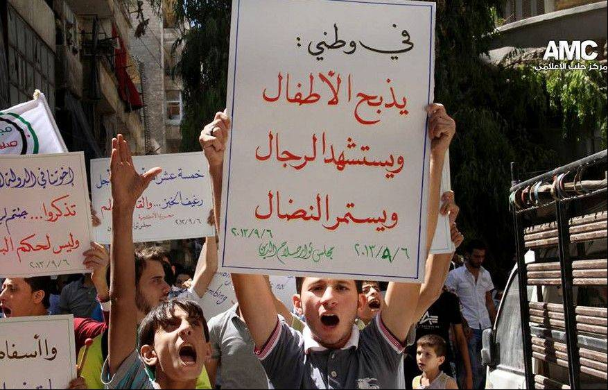 "Protesters hold a poster in Arabic that reads, ""In my country: children are being butchered, men become martyrs, and the struggle continues,"" during a Friday demonstration in Aleppo, Syria."