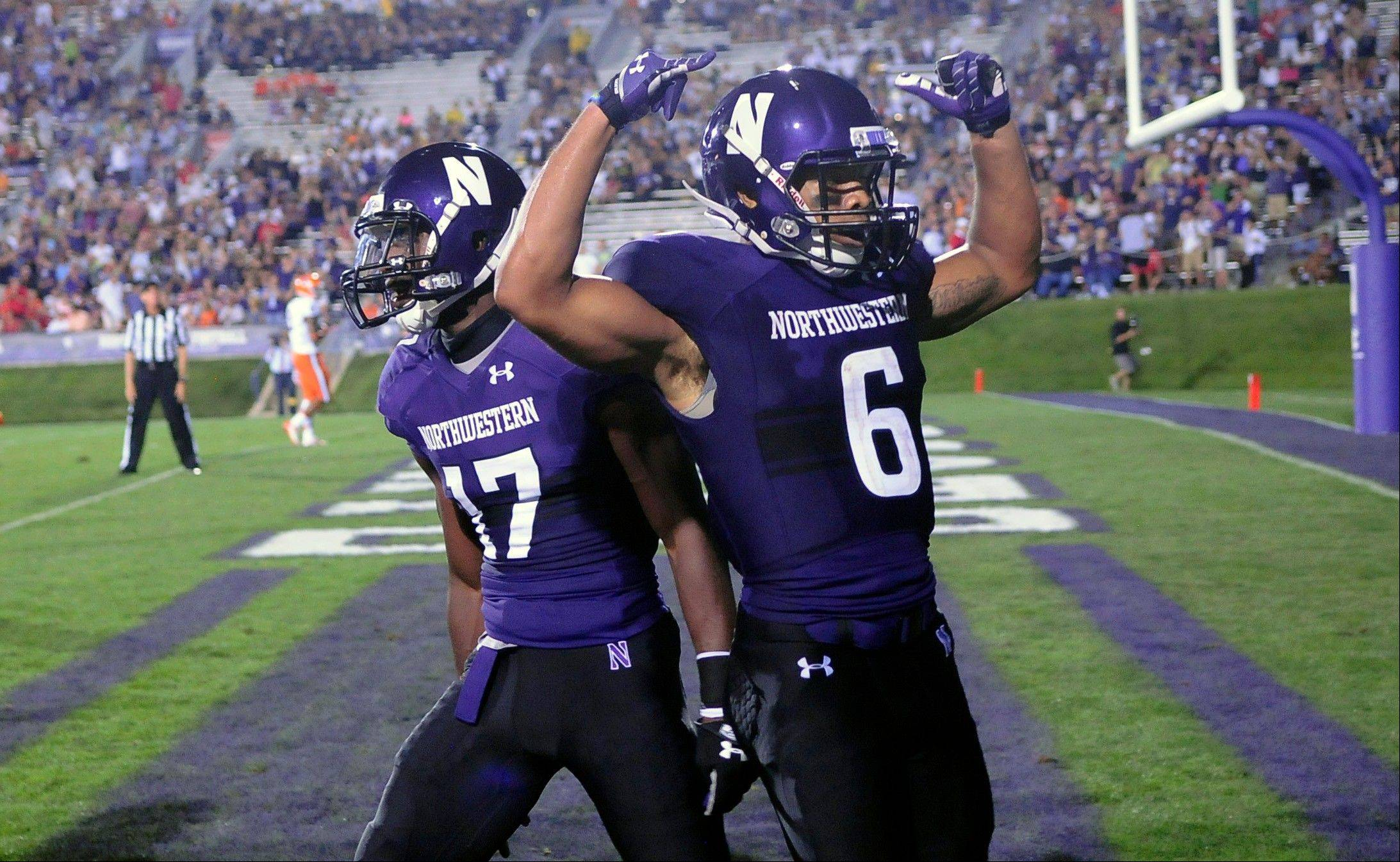 Northwestern's Tony Jones, (6), celebrates his touchdown with teammate Rashad Lawrence, (17) in the second half of an NCAA college football game against Syracuse University in Evanston, Ill, Saturday, Sept.7, 2013