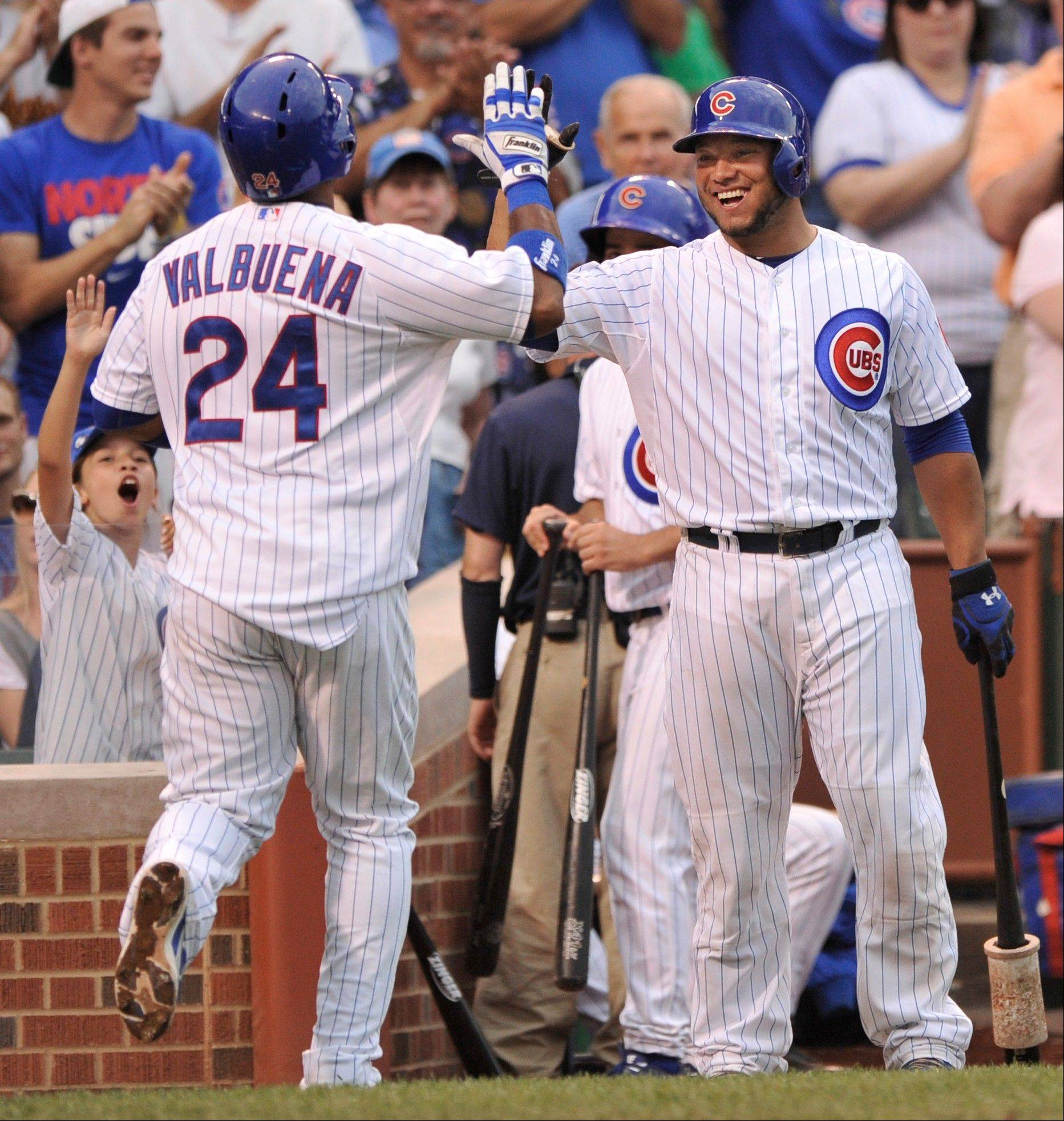 The Cubs' Luis Valbuena (24) celebrates with teammate Welington Castillo after hitting a two-run home run during the second inning Saturday at home against the Milwaukee Brewers.