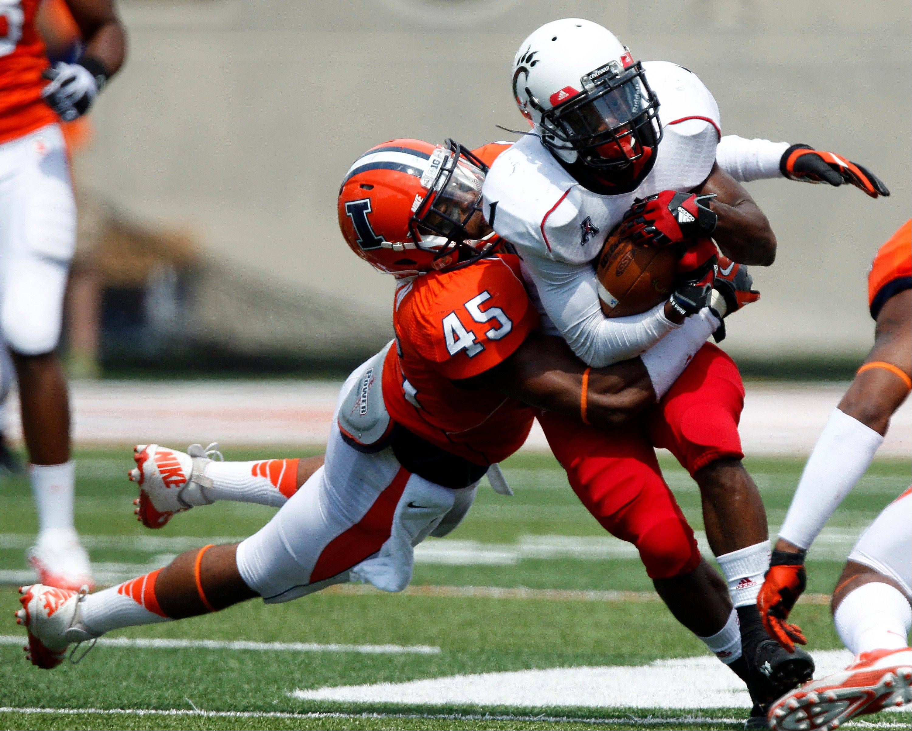 Cincinnati Bearcats running back Ralph Abernathy is tackled by Illinois linebacker Jonathan Brown during the first half Saturday in Champaign.