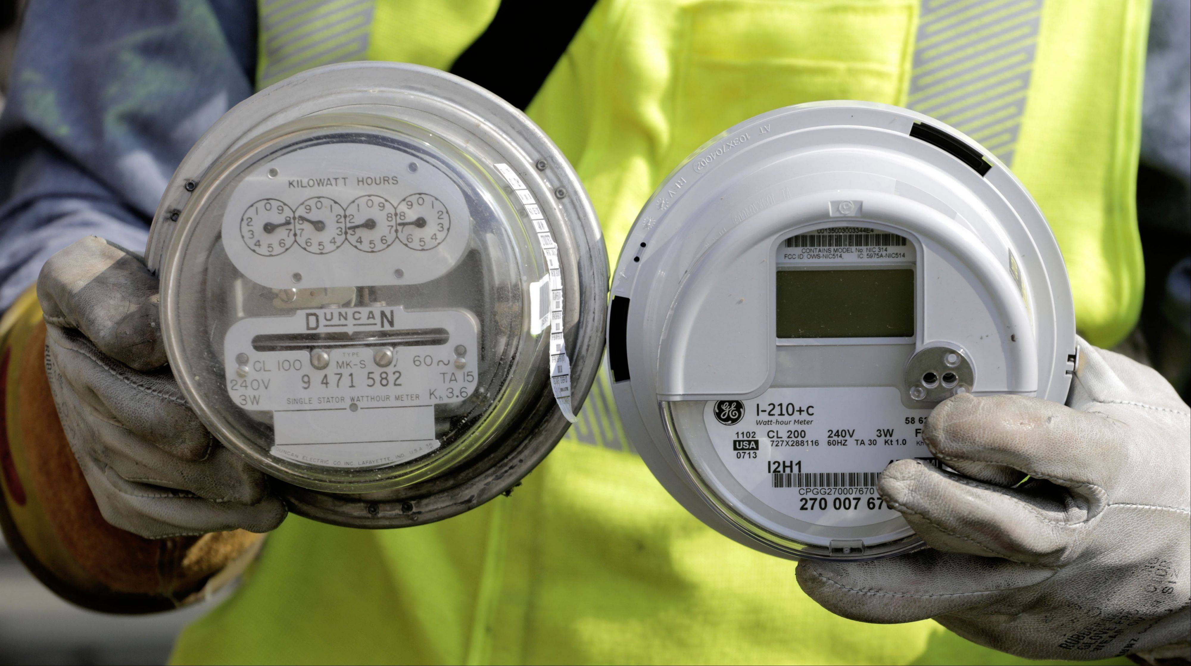 Brian Malloy, a senior energy technician for Commonwealth Edison, holds a standard electricity meter, left, and a new �smart� meter. The new meter is a wireless devices that relays information on electricity consumption directly to the utility.