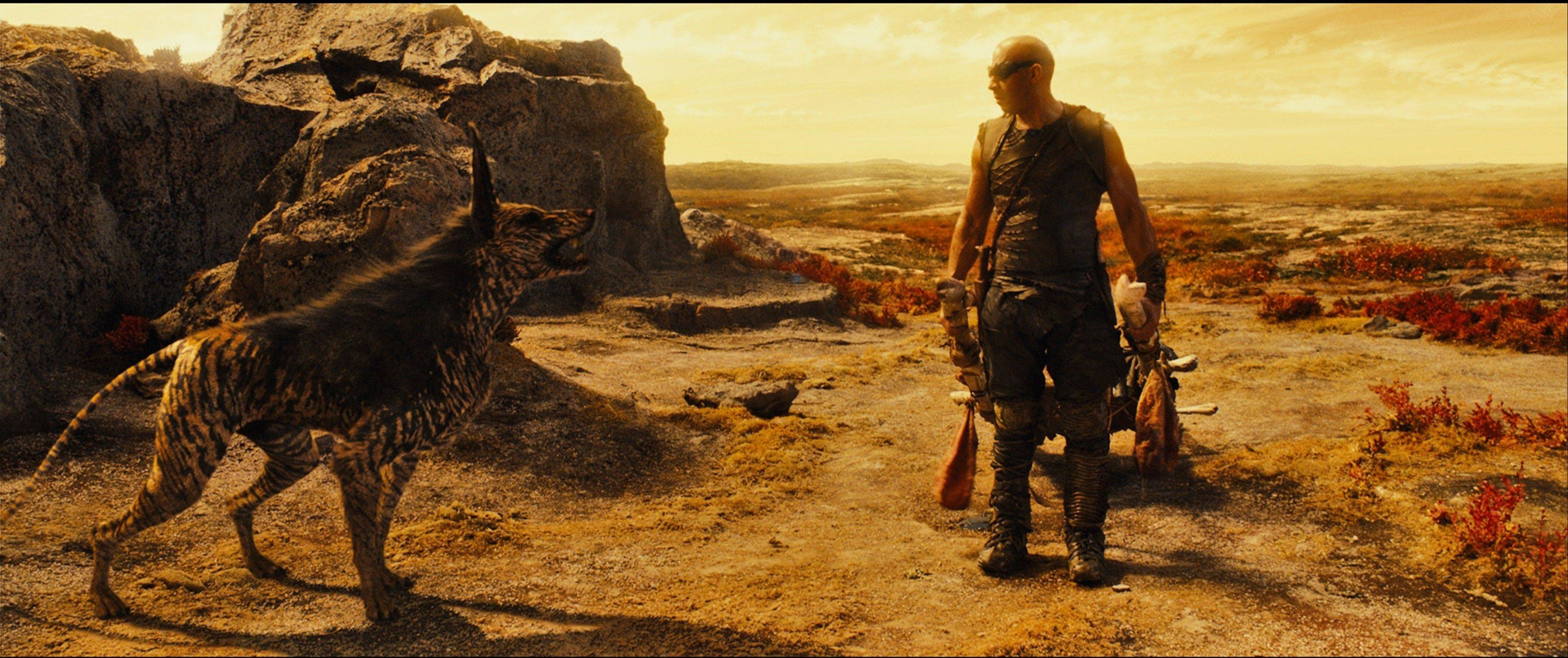 "Riddick (Vin Diesel) befriends a weird zebra/wolf creature on a sepiatone planet in David Twohy's thriller ""Riddick."""