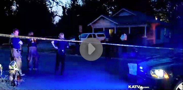 In an image made from video provided by KATV, police surround a home in Pine Bluff, Ark., Saturday during a standoff that left a 107-year-old man dead.