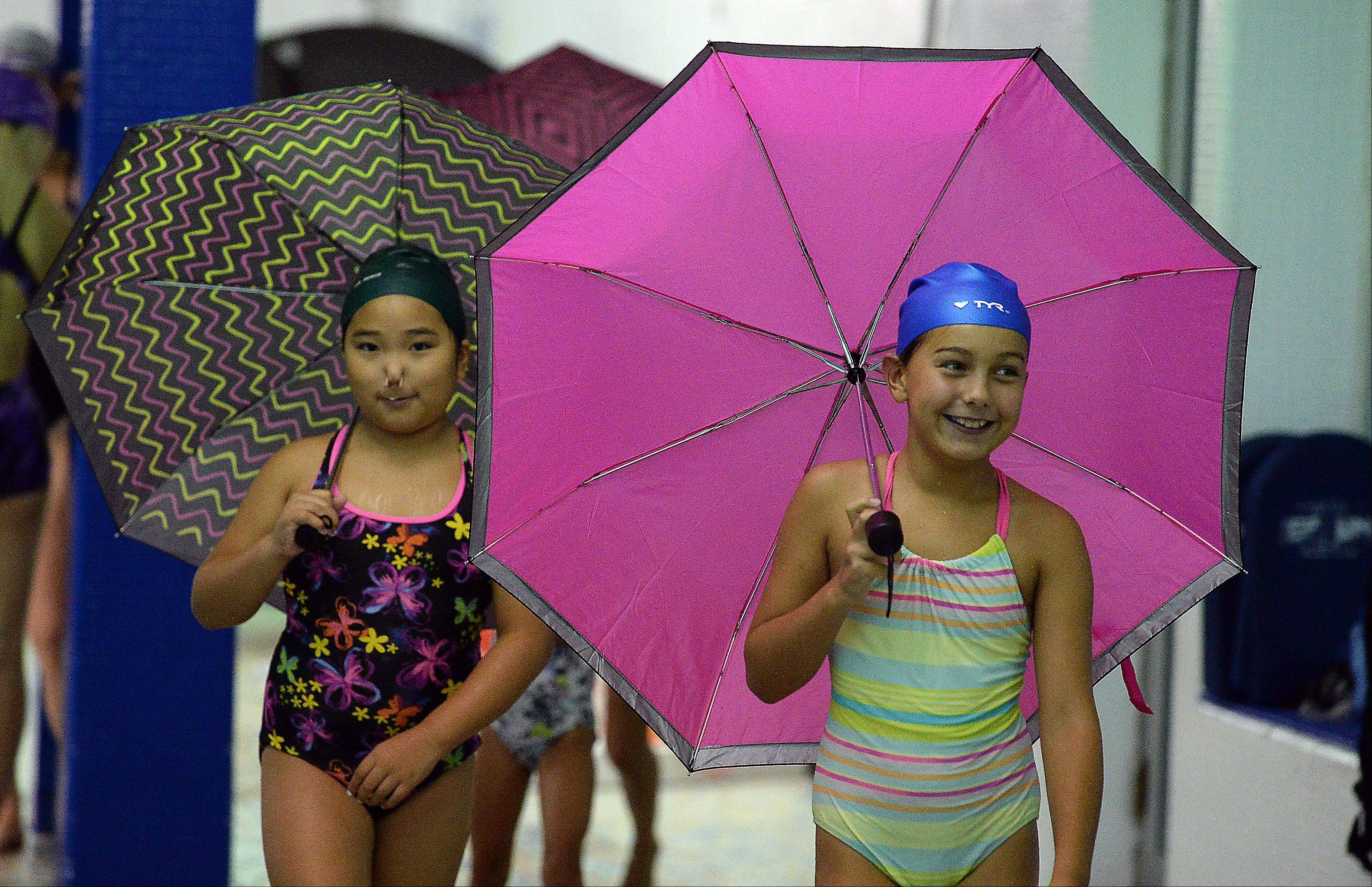 "Chaewon Park, 10, of Mount Prospect, left, and Lexi Dorula, 9, of Prospect Heights lead the rest of the AquaSprites as they practice their synchronized swimming to the song ""Singin' in the Rain"" by Gene Kelly at the Lattof YMCA."
