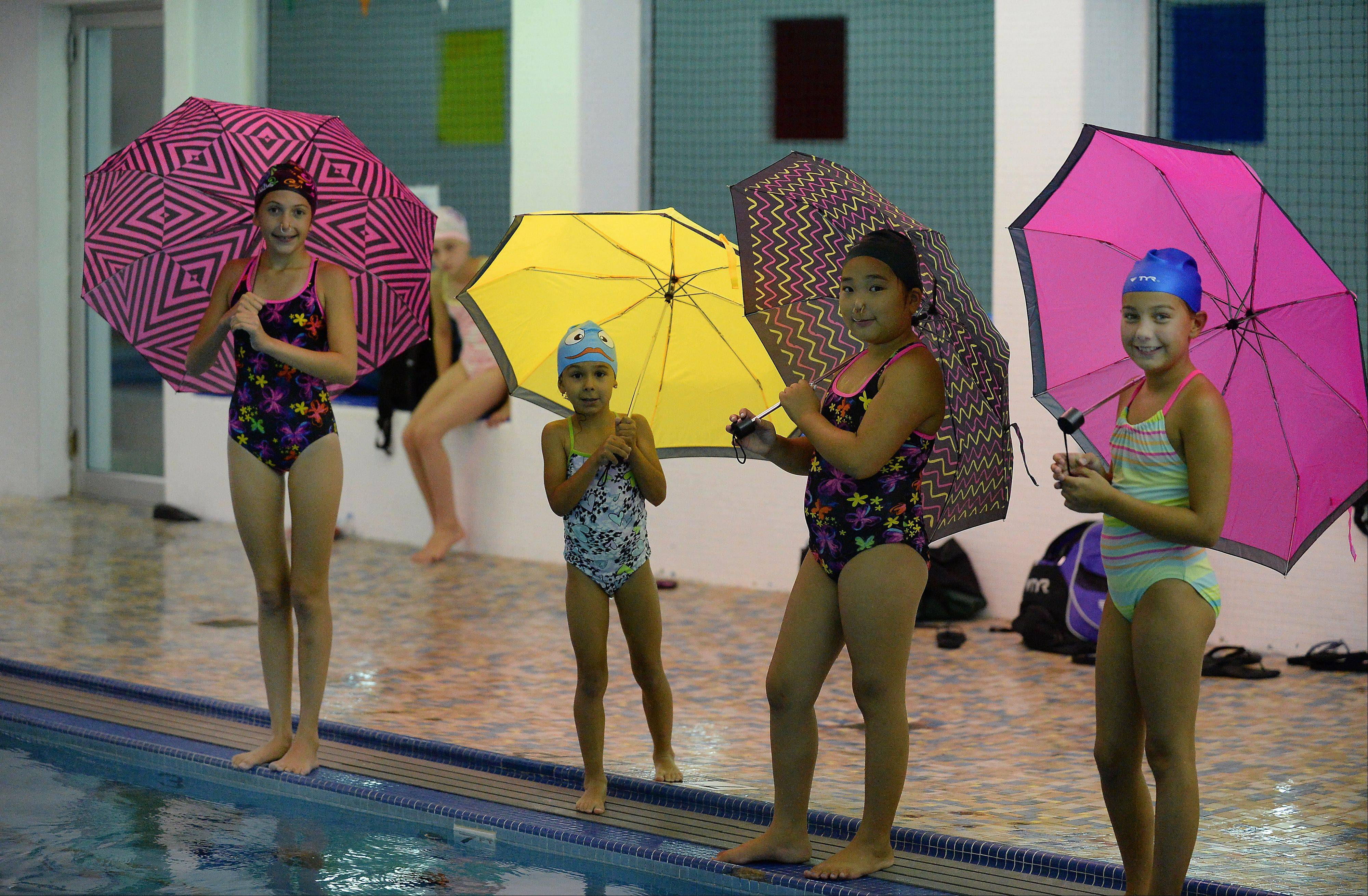 "From left, Olivia Vasilakopoulos, 11, of Park Ridge, Melanie Angelov, 6, and Chaewon Park, 10, both of Mount Prospect and Lexi Dorula, 9, of Prospect Heights, get ready to practice their ""Singin' in the Rain"" synchronized swimming routine at the Lattof YMCA."