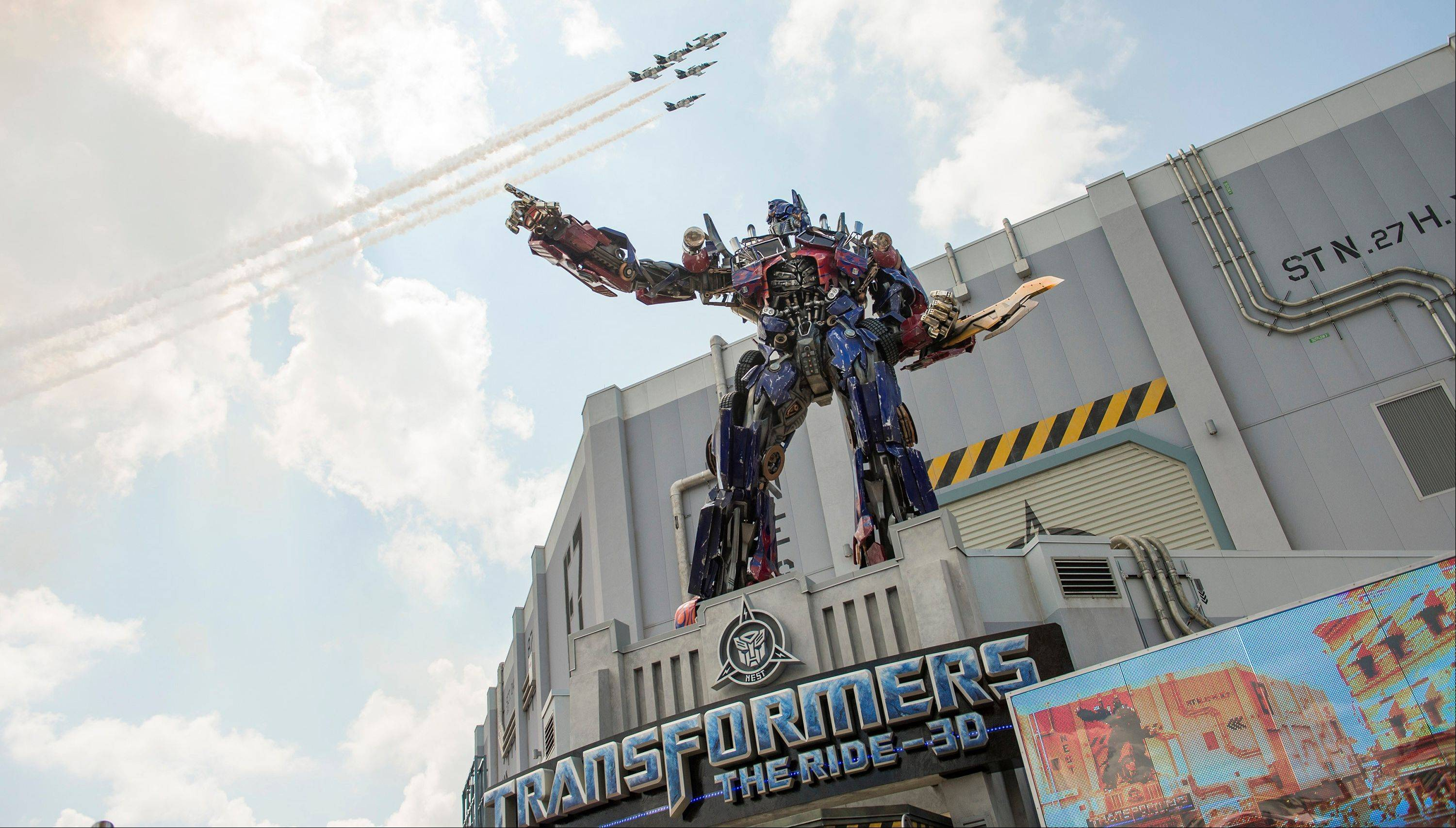 A three-story-tall Optimus Prime stands at the entrance to the Transformers: The Ride-3D as private jets fly overhead at Universal Orlando Resort in Orlando, Fla.