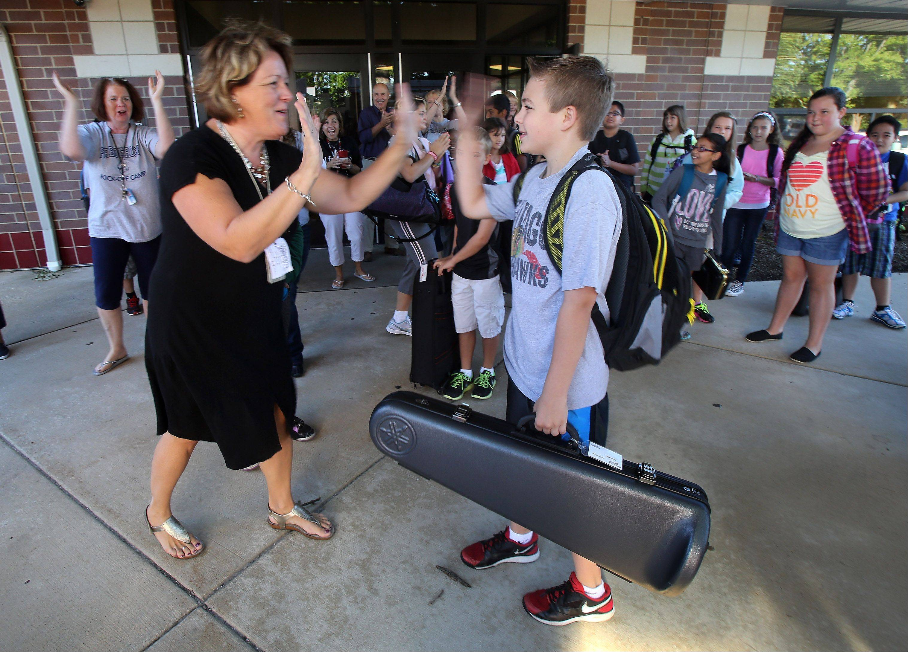 Fifth grade teacher Darlene Placko gives a high five to Caden Moe, of Grayslake, after he received a ride on a Grayslake Fire Department truck Tuesday to Frederick School. Moe won a raffle prize at the end of the Kick Off Camp for 175 new students.