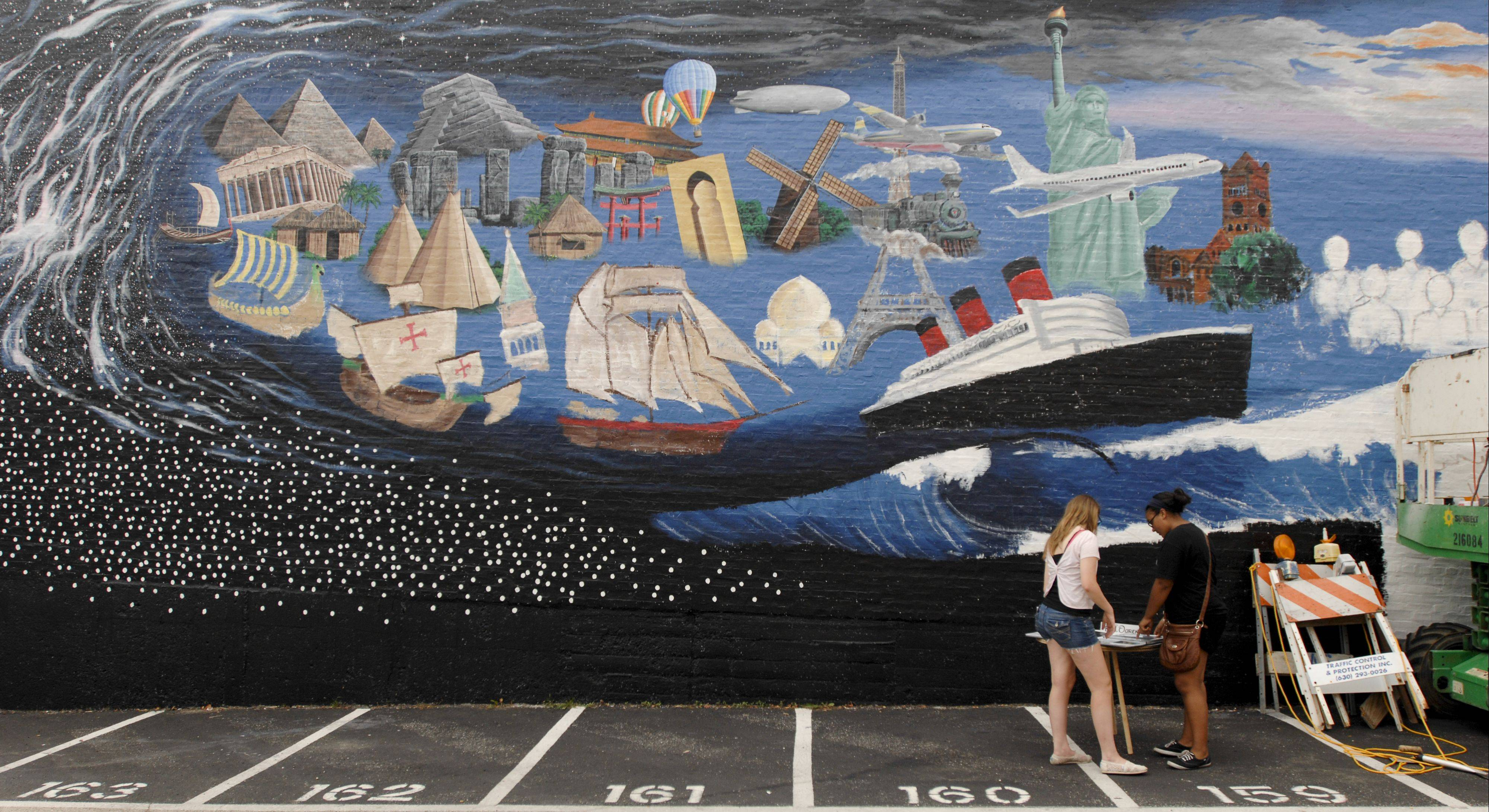 "Wheaton residents and others were invited to sign a star on the mural ""Pearls of the Universe"" Sunday. The mural, by retired Disney artist R.J. Ogren, of Naperville, celebrates the immigrant journey to Wheaton."