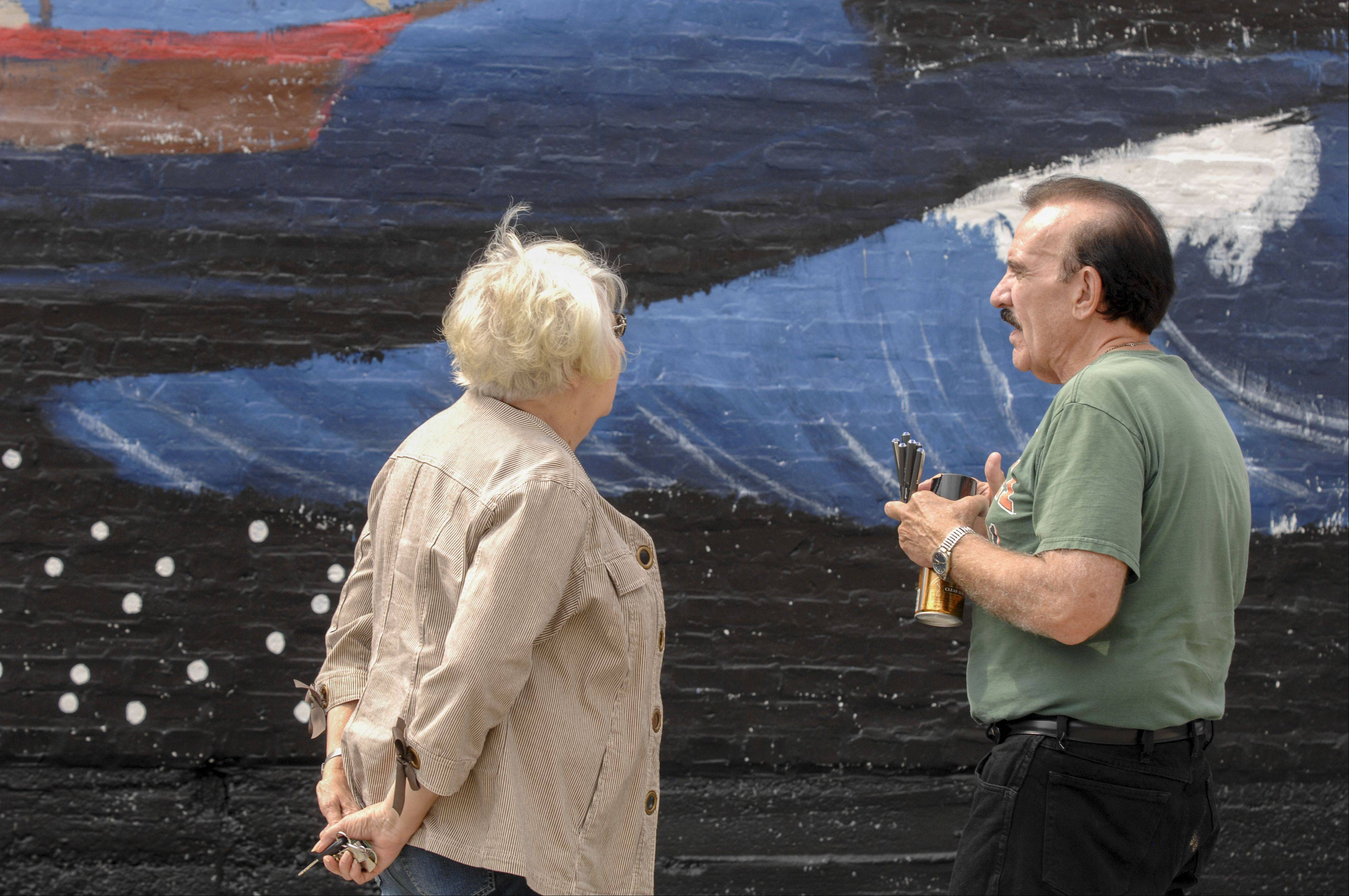"""Pearls of the Universe"" artist R.J. Ogren, right, of Naperville, talks with those coming to sign a star on the mural Sunday. The mural celebrates the immigrant journey to Wheaton."