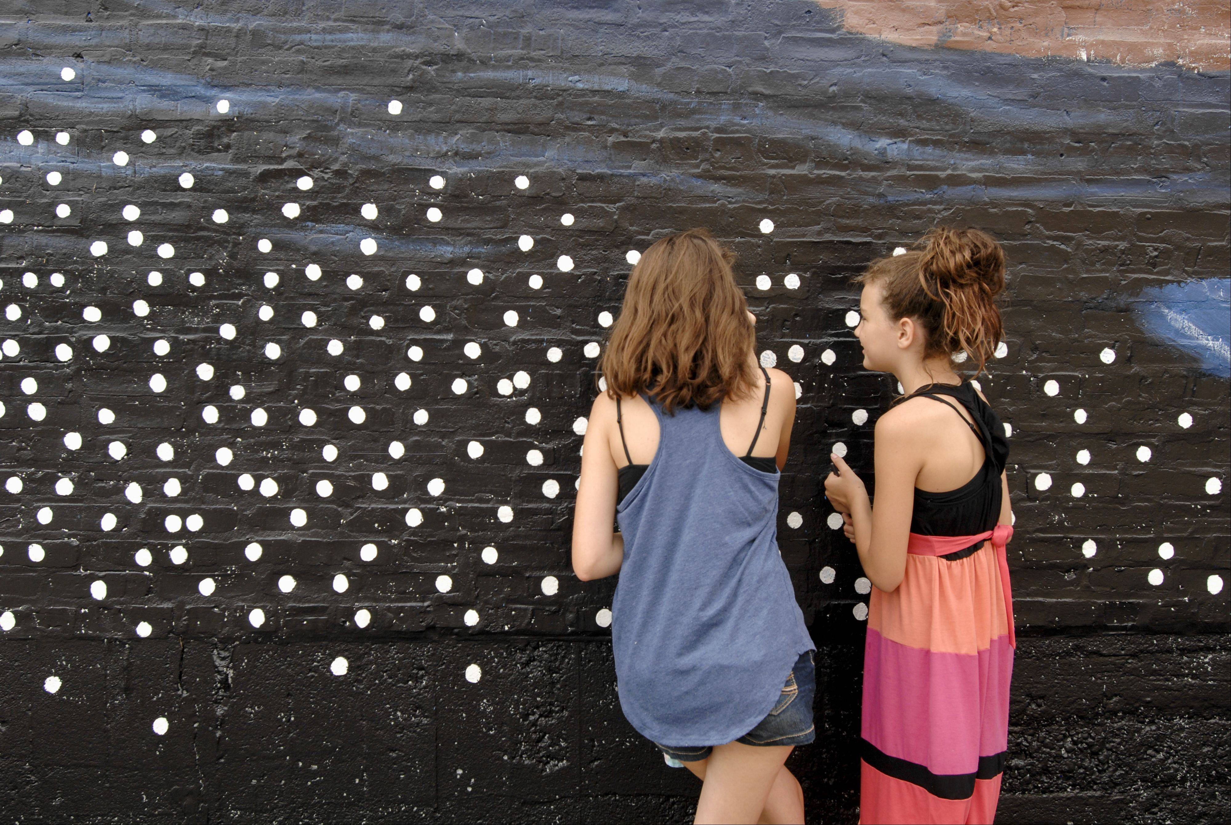 "Wheaton residents Kaity McPherson, 13, and Ana Hyland, 10, sign stars on the mural ""Pearls of the Universe"" by R.J. Ogren on Sunday. The mural celebrates the immigrant journey to Wheaton."
