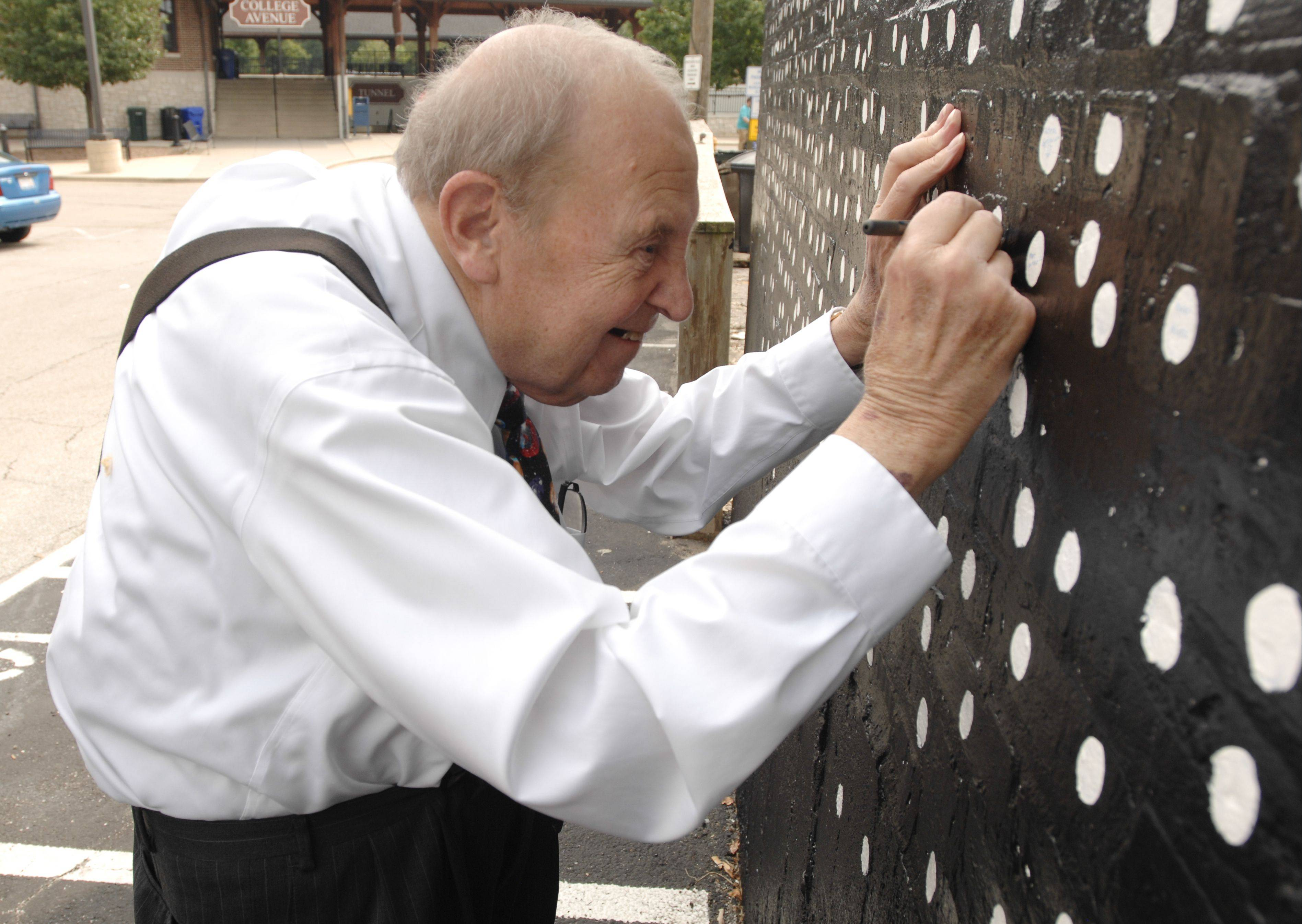 "Lifelong Wheaton resident and patron Lewis Morgan signs a star on the mural ""Pearls of the Universe"" by R.J. Ogren on Sunday. The mural celebrates the immigrant journey to Wheaton."