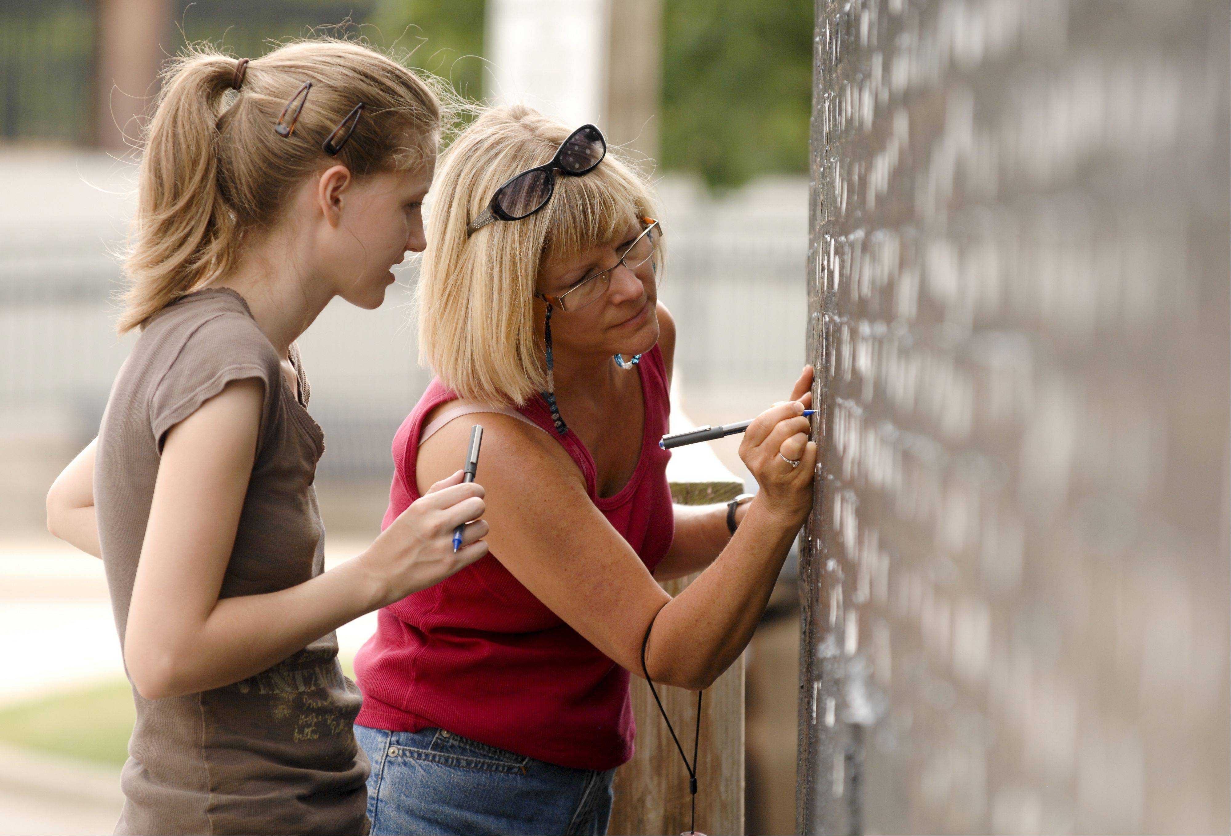 "Wheaton residents Christine and Louanne Irving, right, sign stars on the mural ""Pearls of the Universe"" by R.J. Ogren on Sunday. The mural celebrates the immigrant journey to Wheaton."