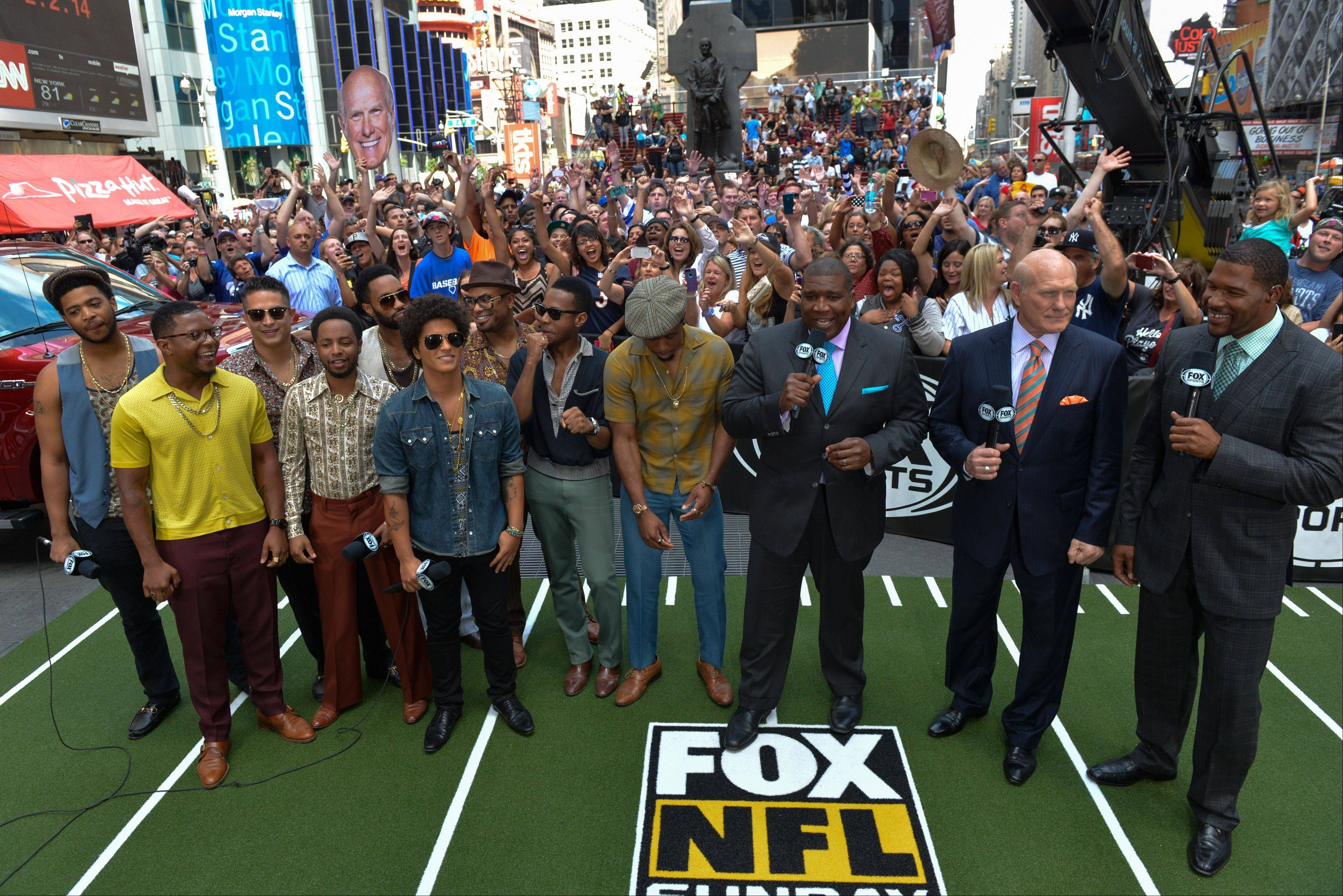 This image released by the NFL shows Bruno Mars, fifth from left, with Curt Menefee, from third right, Terry Bradshaw and Michael Strahan in Times Square after it was announced Sunday, Sept. 8, 2013, on 'Fox NFL Sunday' that he will play during the Pepsi Super Bowl XLVIII Halftime Show at MetLife Stadium in East Rutherford, N.J. on Feb. 2, 2014.