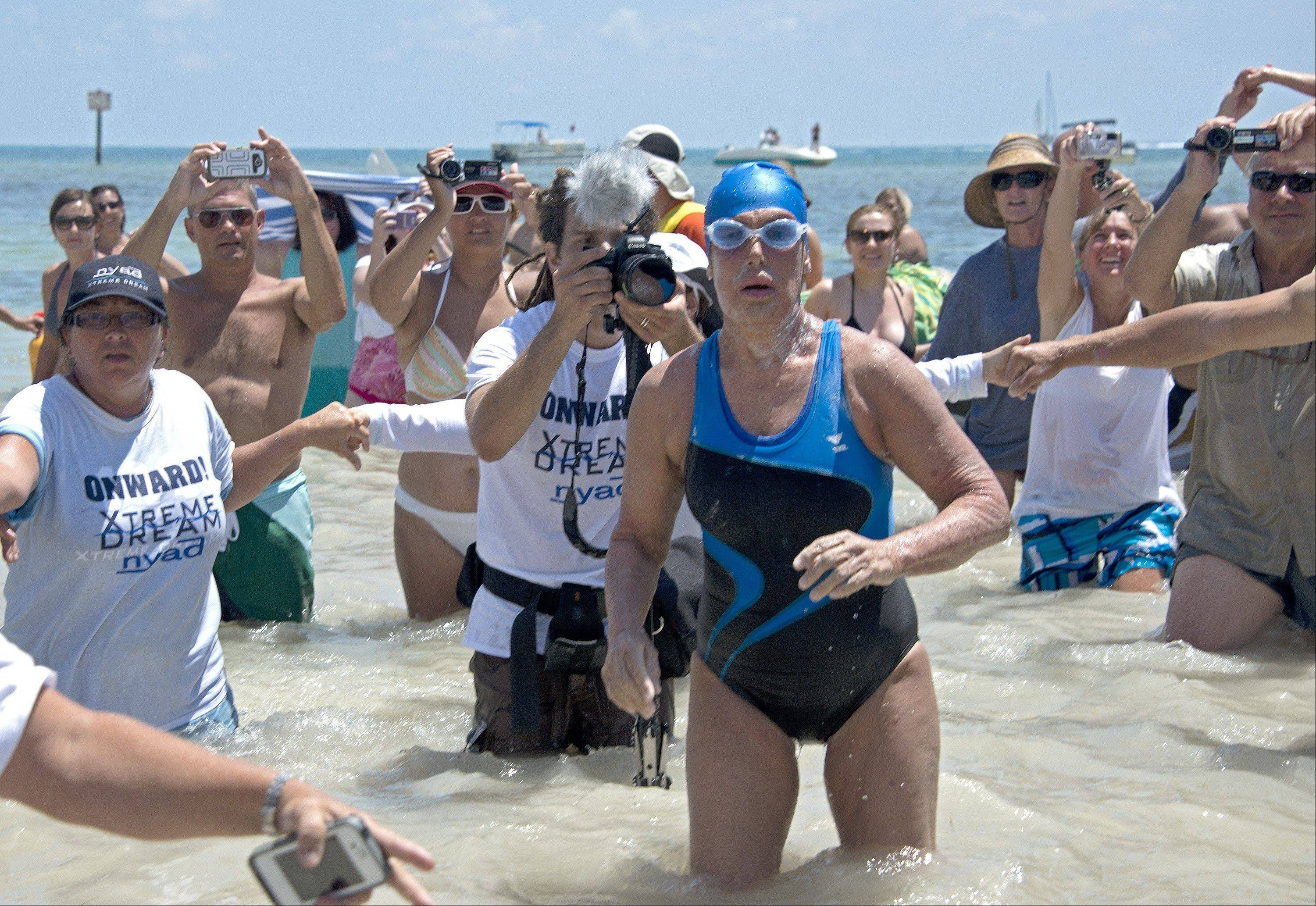 Diana Nyad emerges from the Atlantic Ocean after completing a 111-mile swim from Cuba to Key West, Fla., Sept. 2.