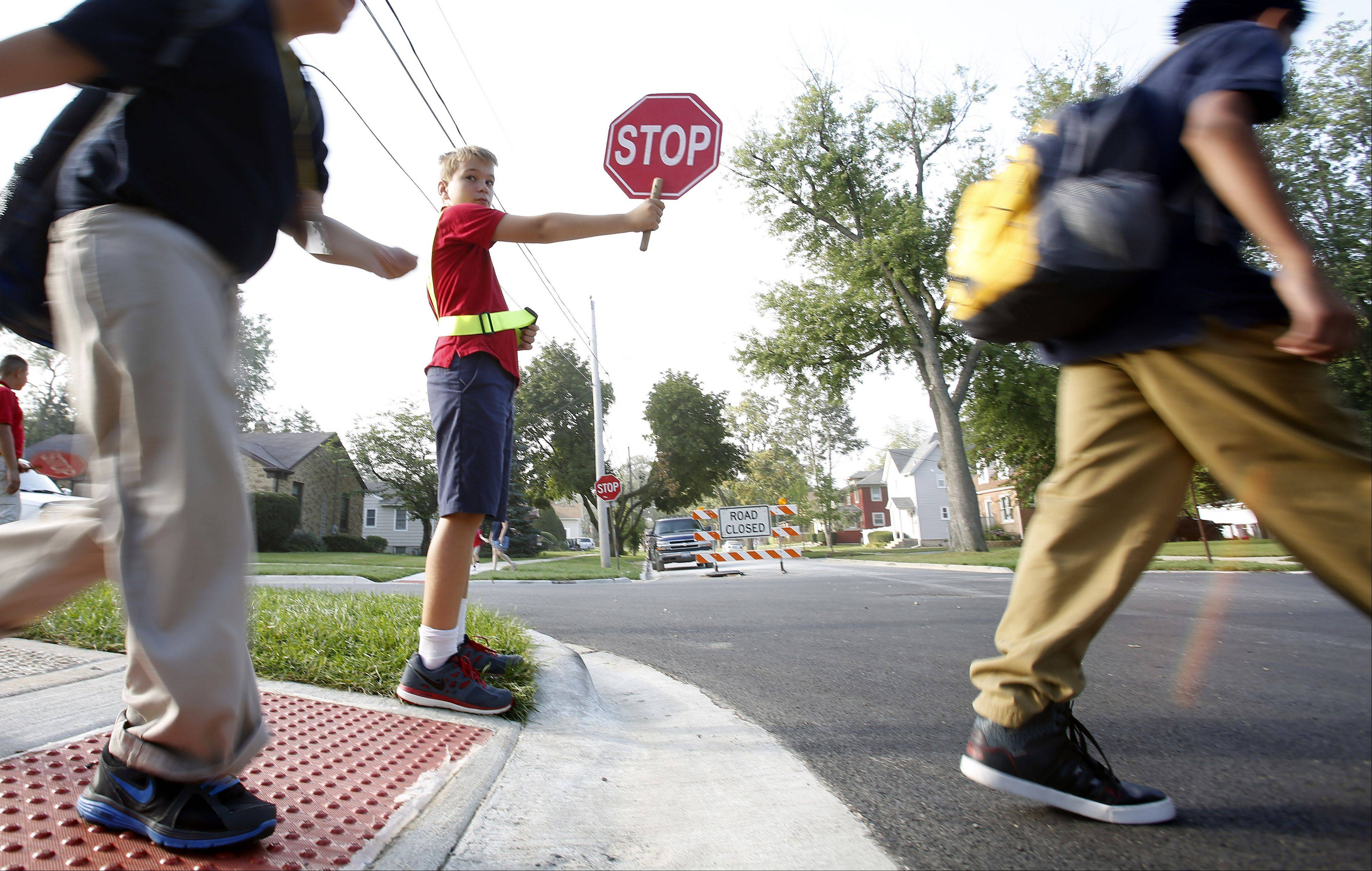 Jakob Scham, 10, volunteers as a crossing guard before school, and his mom says that he has really blossomed since he switched from private school to Washington, though the Elgin school has been identified for federal restructuring because of poor performance.