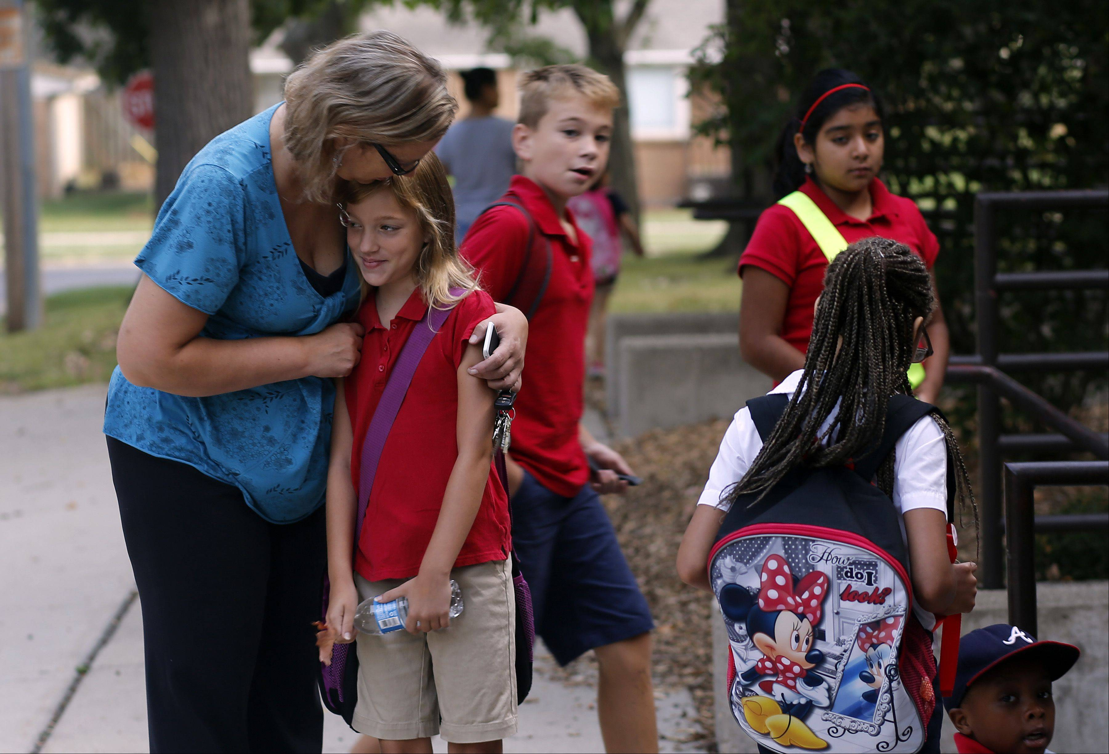 Linda Scham of Elgin gives daughter Kayla, 9, a big hug before class starts at Washington Elementary School in Elgin. Her son, Jakob, 10, walks directly behind them. Washington is one of 10 U-46 schools undergoing federal restructuring because of poor performance.