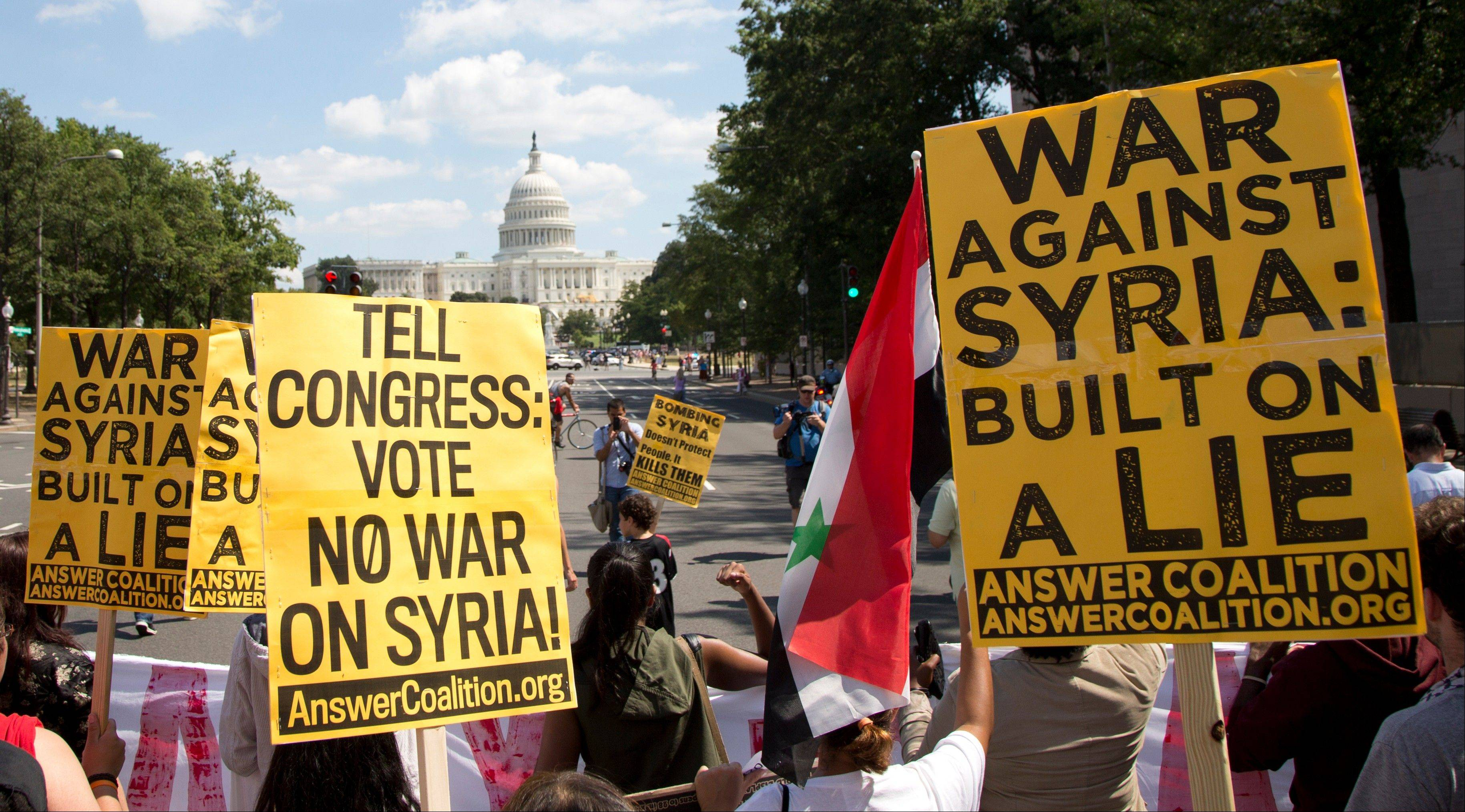 Protesters against U.S. military action in Syria march to Capitol Hill Saturday from the White House in Washington.