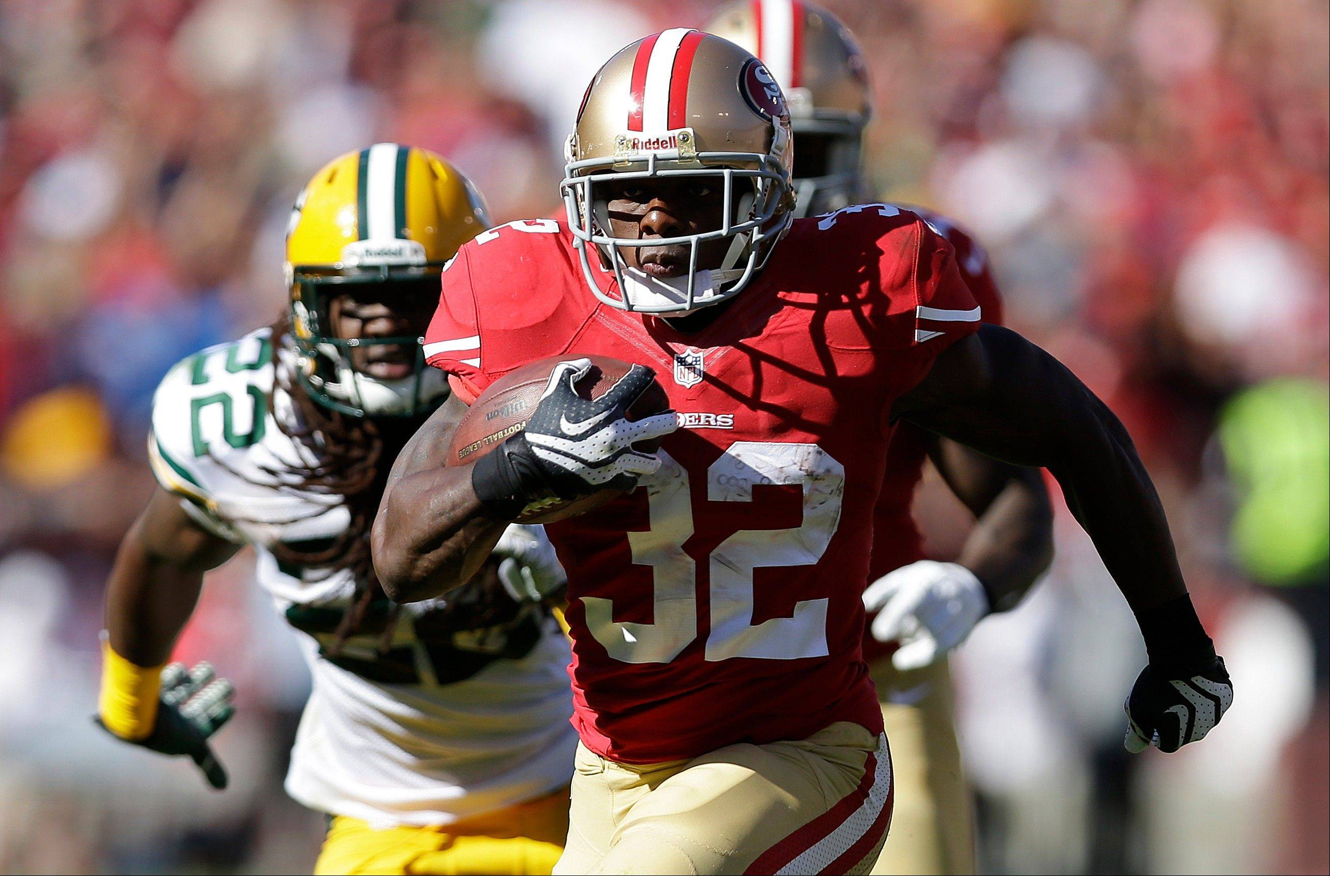 San Francisco 49ers running back Kendall Hunter (32) runs past Green Bay Packers defensive back Jerron McMillian (22) during the fourth quarter of an NFL football game in San Francisco, Sunday, Sept. 8, 2013.