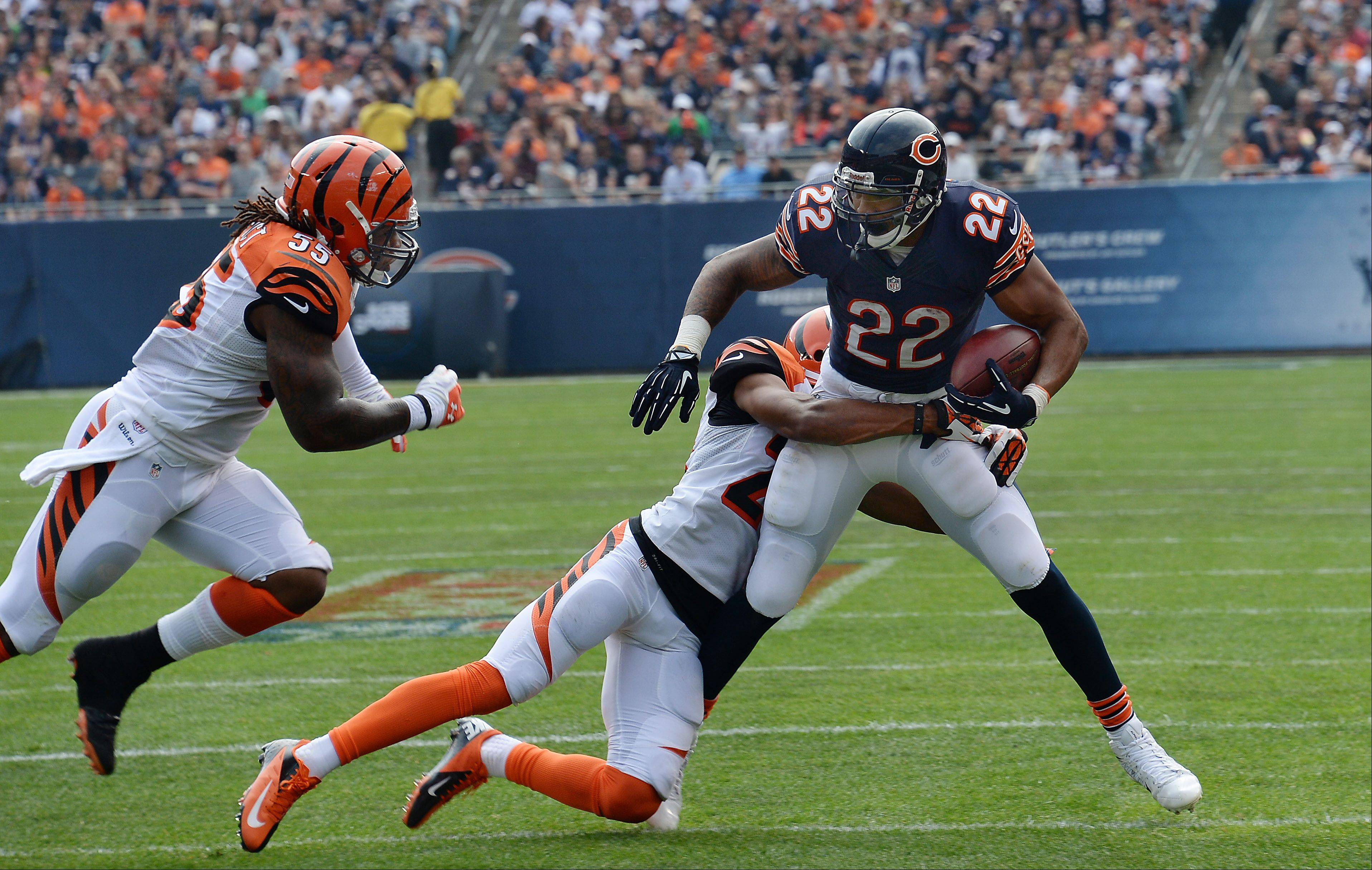 Chicago Bears Matt Forte runs for short yardage as he is tackled by Bengals Leon Hall in the first half of the season opener against the Cincinnati Bengals at Soldier Field in Chicago on Sunday.