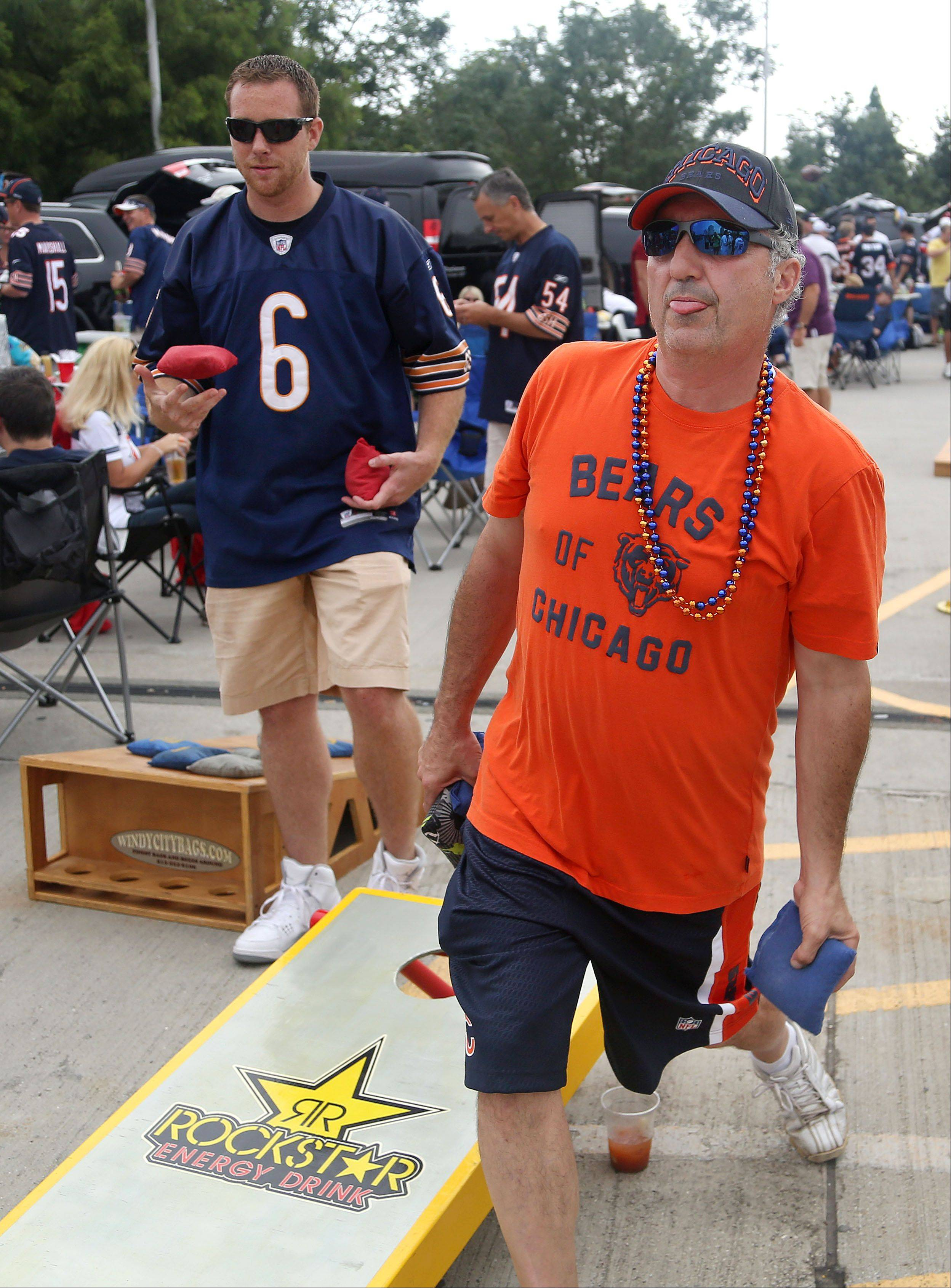 Steven Salidas of Lombard, right, and Casey Lewis of Lake Villa play baggo prior to the Bears opening day game against the Cincinnati Bengals Sunday at Soldier Field in Chicago