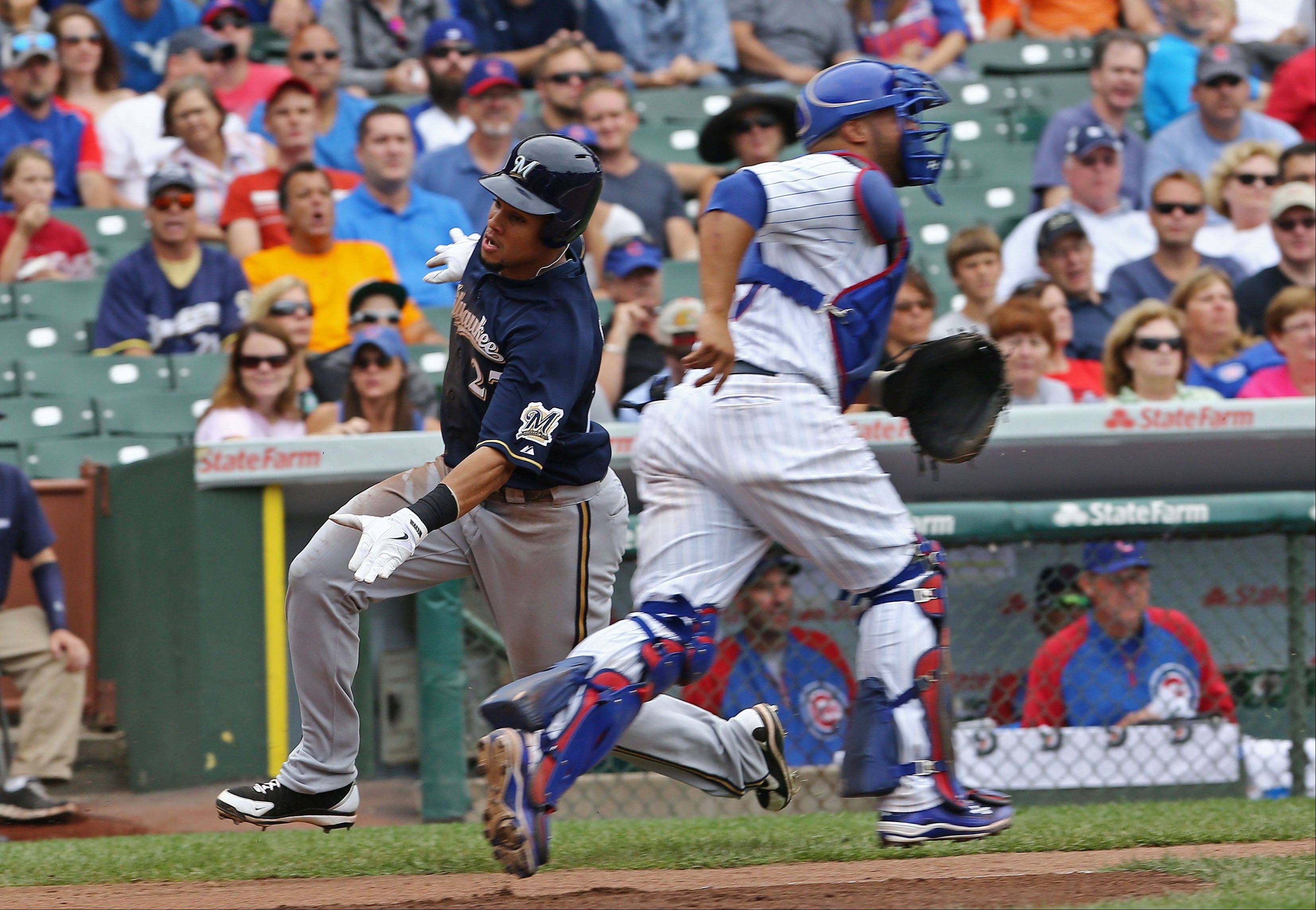 Milwaukee Brewers' Carlos Gomez slides past Chicago Cubs catcher Wellington Castillo to score in the seventh inning during a baseball game in Chicago on Sunday, Sept. 8, 2013.