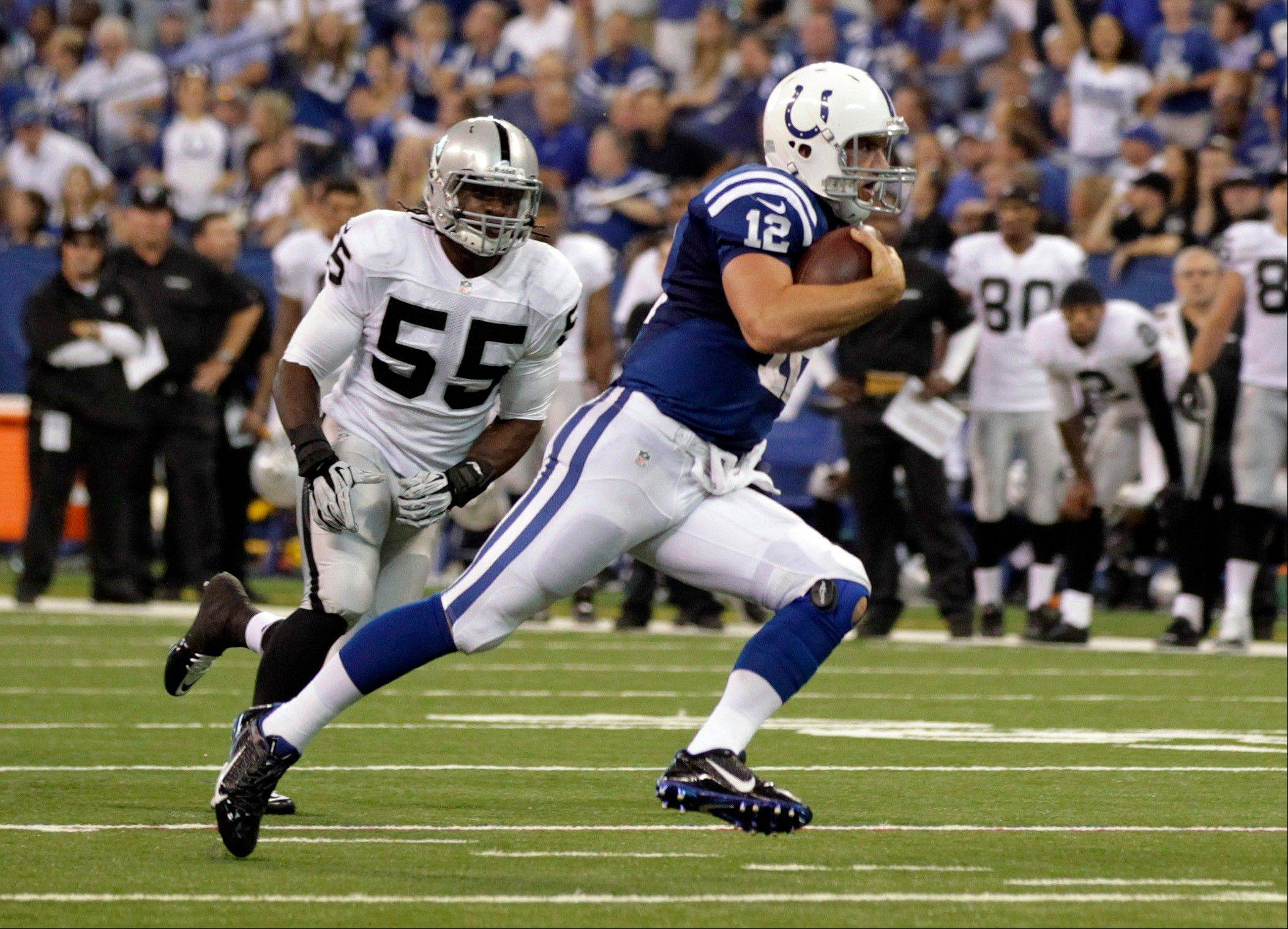 Indianapolis Colts quarterback Andrew Luck runs past Oakland Raiders outside linebacker Sio Moore on his way to a touchdown during the second half of an NFL football game in Indianapolis, Sunday, Sept. 8, 2013.