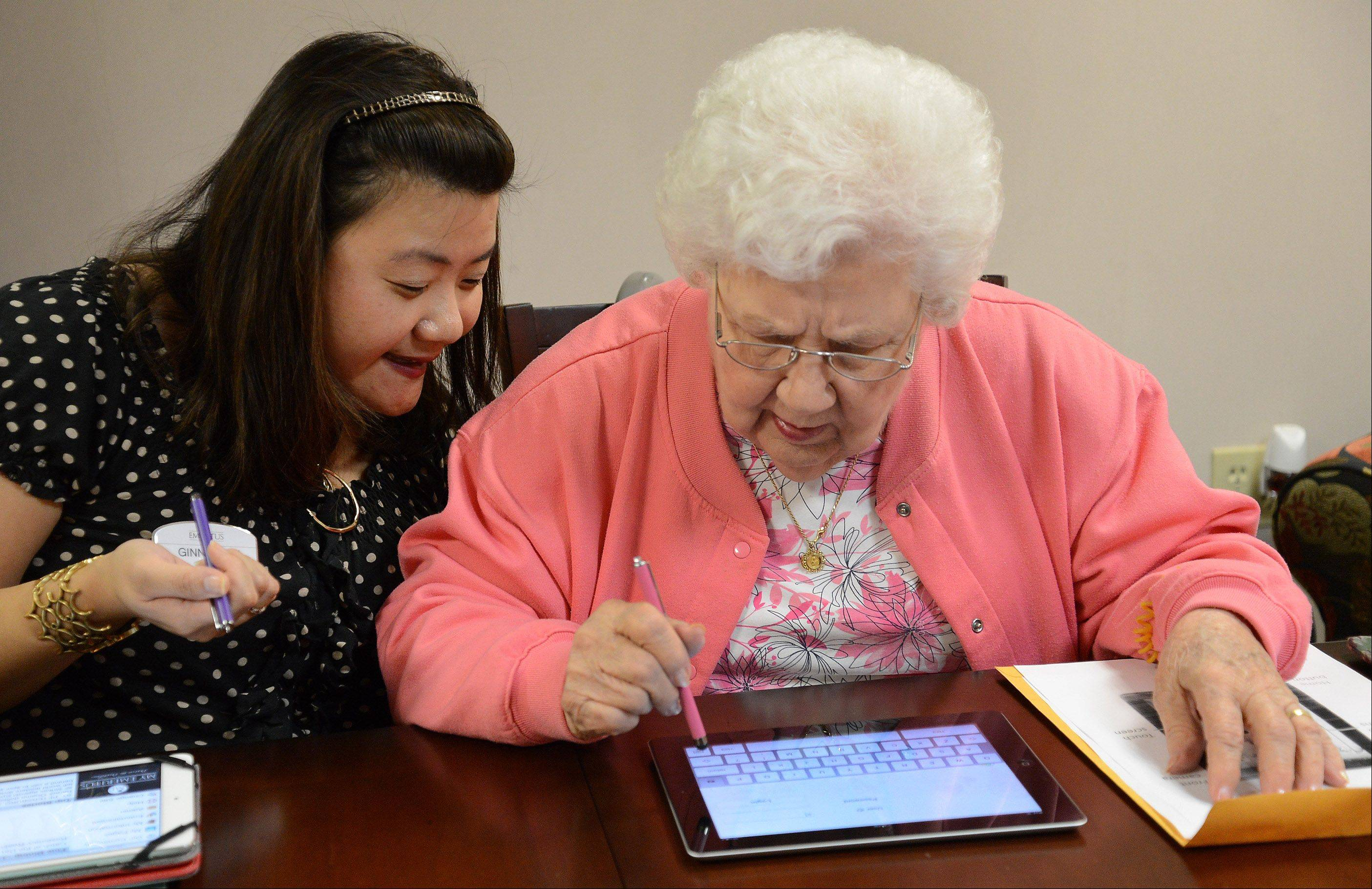 Sending her first email by tapping on a photo, Simone Lucas, right, uses a new iPad app created especially for the residents at Emeritus Senior Living. The new app will make seniors at the Hoffman Estates center more social, says Ginna Baik, left, director of innovation and resident technology.