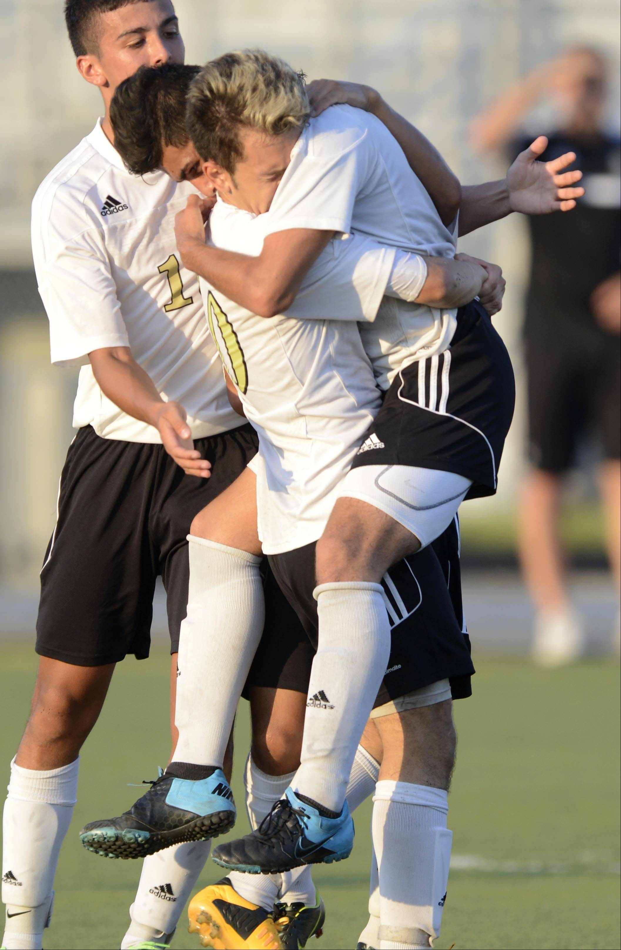 Streamwood�s Christian Vences is picked up by teammate Nestor Ascencio after Vences scored the first goal against Kaneland Monday in Streamwood. Teammate Christian Balbino also arrives for the celebration.