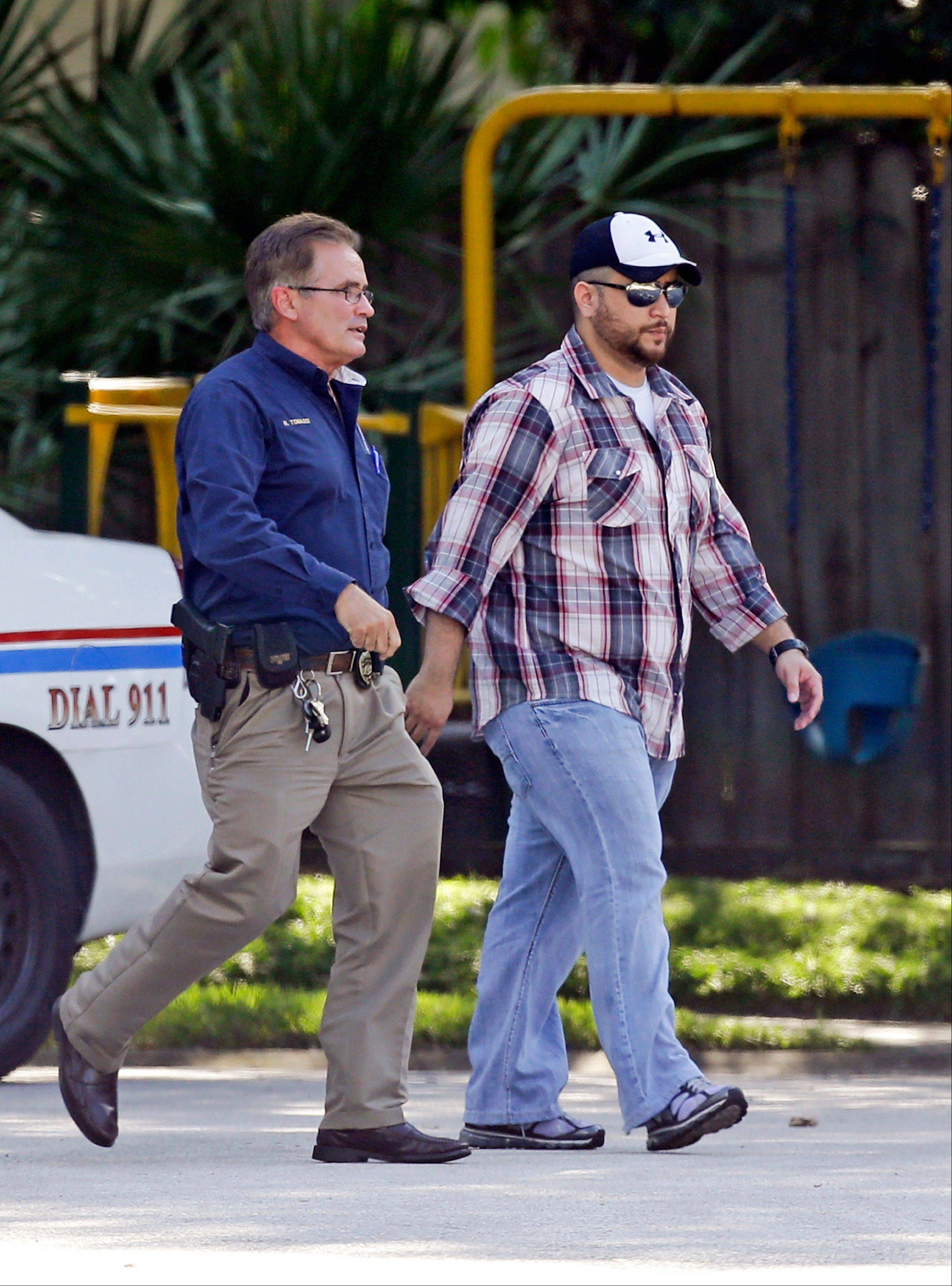 George Zimmerman, right, is escorted to a home by a police officer Monday in Lake Mary, Fla., after a domestic incident in the neighborhood where Zimmerman and his wife Shellie had lived during his murder trial.