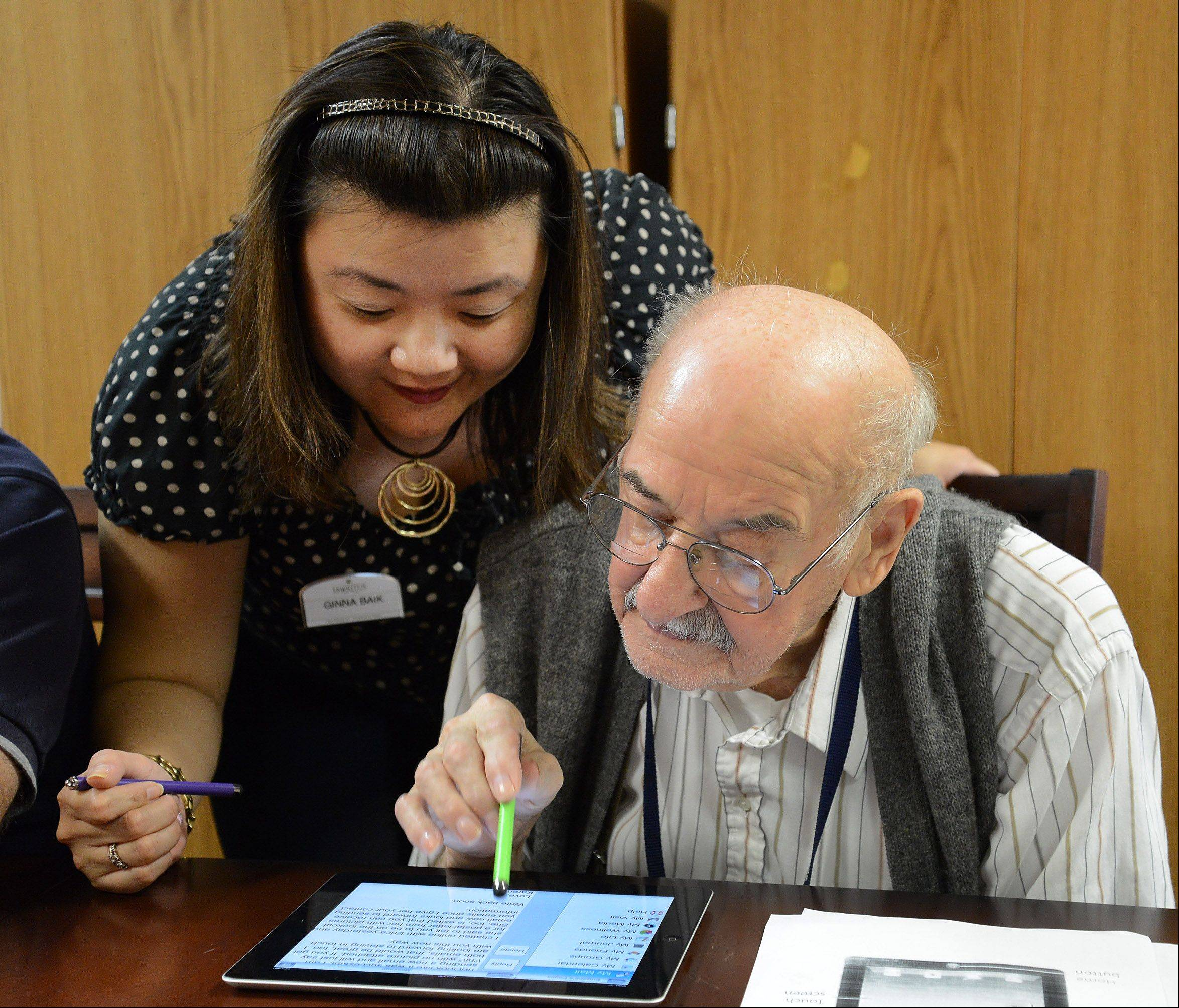 Using an iPad app designed for seniors, Emeritus Senior Living resident Eugene Keszycki, 89, of Hoffman Estates opens an email featuring a photo of his granddaughter, as Ginna Baik, Emeritus's director of innovation, offers her help.