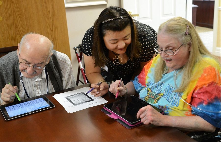 Even if you are old enough to remember life before computers, being comfortable with the online world is a must, says Ginna Baik, center, director of innovation for Emeritus Senior Living. Baik helps Eugene Keszycki, left, and Kathleen Dammjanovic with their new iPad apps.