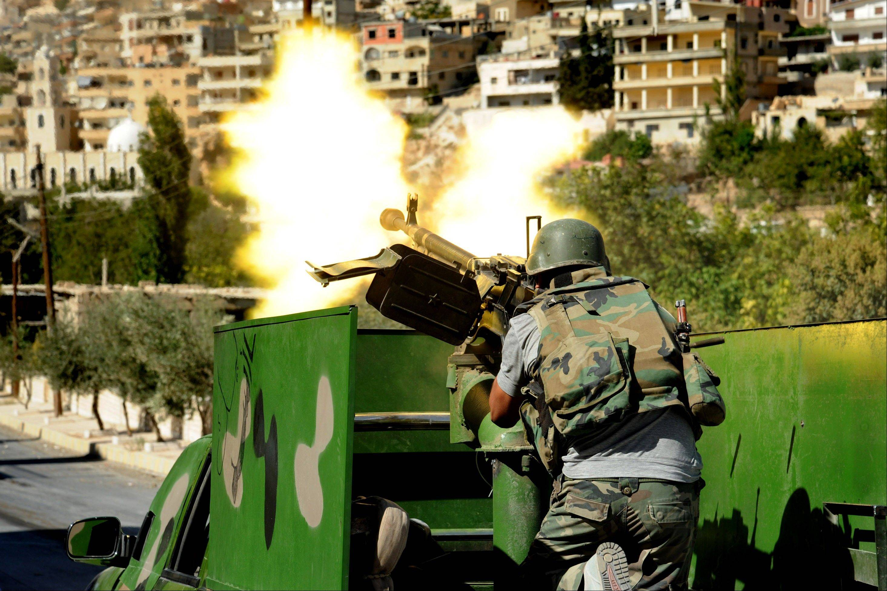 In this photo released Saturday by the Syrian official news agency SANA, a Syrian military soldier fires a heavy machine gun during clashes with rebels in Maaloula village, northeast of the capital Damascus, Syria. Rebels including al-Qaida-linked fighters gained control of Maaloula, Syrian activists said Sunday. Government media provided a dramatically different account of the battle suggesting regime forces were winning. It was impossible to independently verify the reports from Maaloula, a scenic mountain community known for being one of the few places in the world where residents still speak the ancient Middle Eastern language of Aramaic.