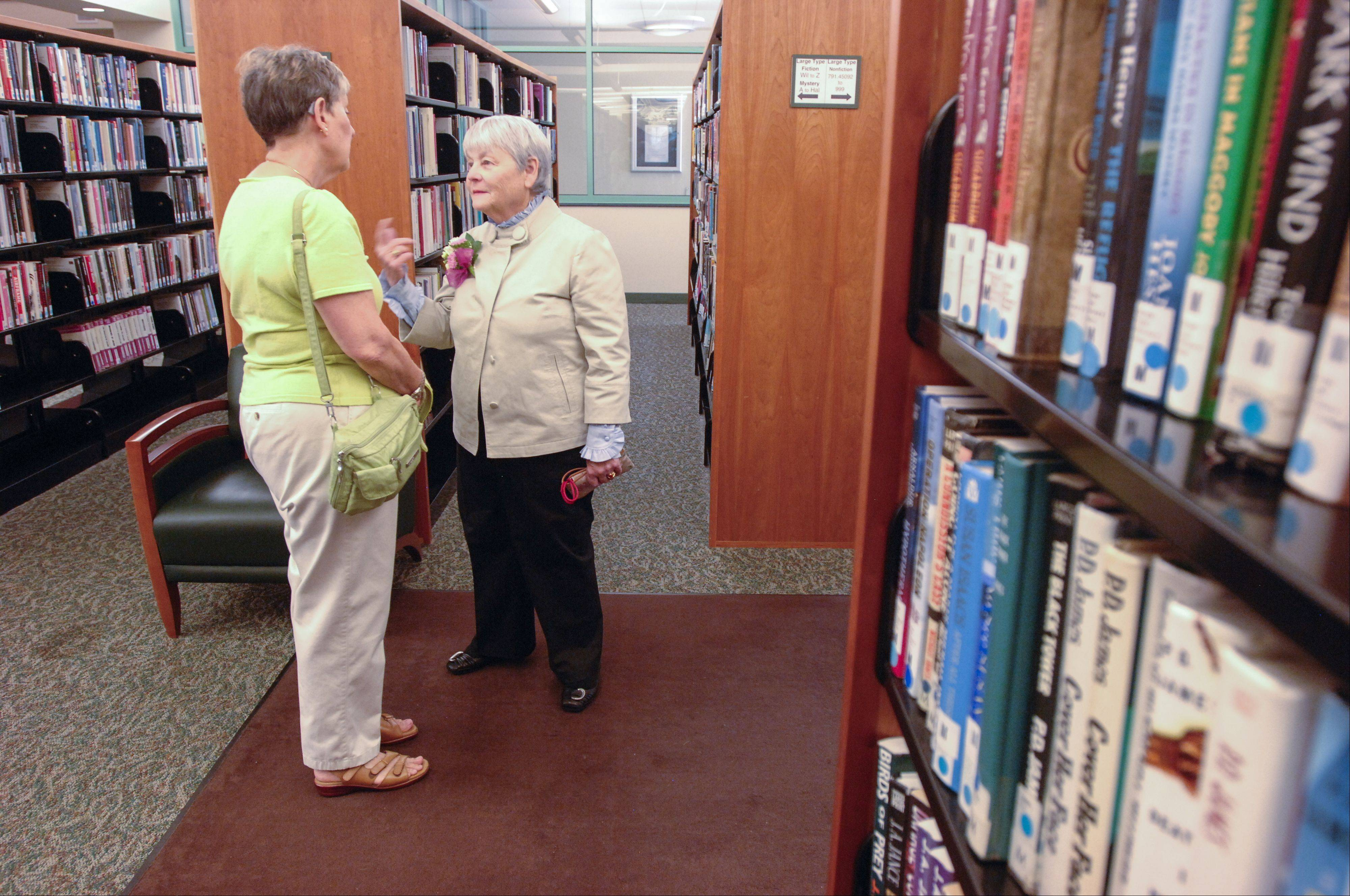 Ruth Sender talks with retiring Wheaton Public Library Director Sarah Meisels, right, during the a party Sunday to honor Meisels' 47 years of service with the library.