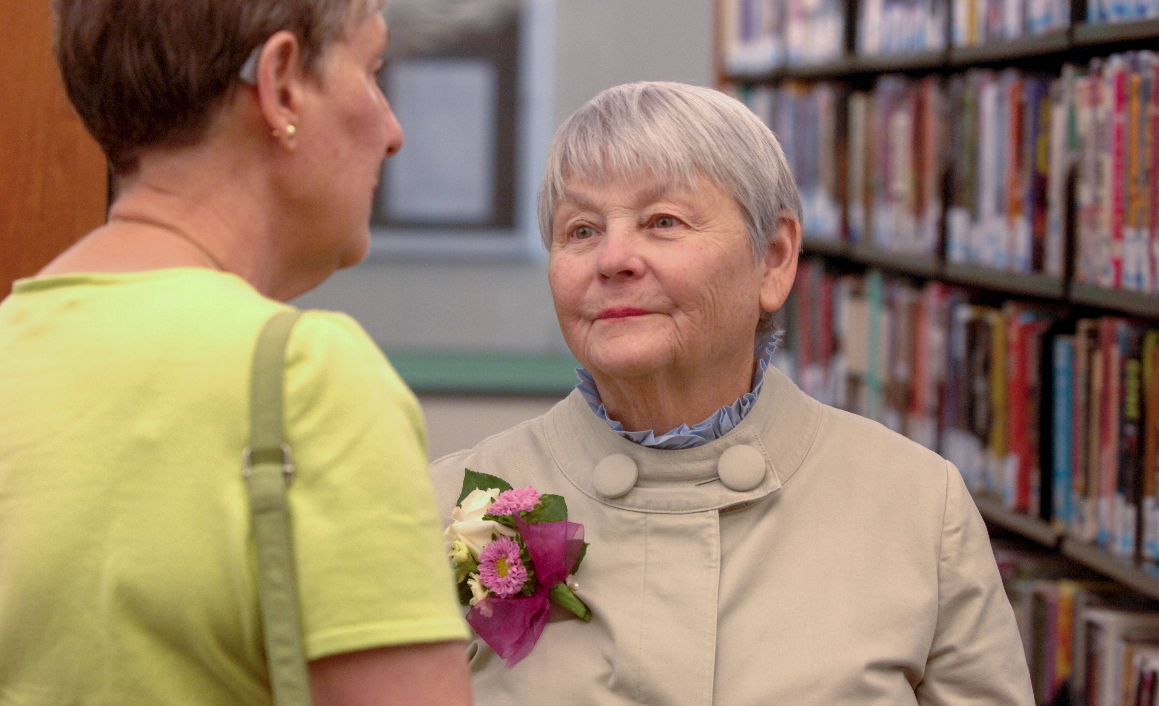 Ruth Sender talks with retiring Wheaton Public Library Director Sarah Meisels, right, during a party Sunday to honor Meisels' 47 years of service with the library.
