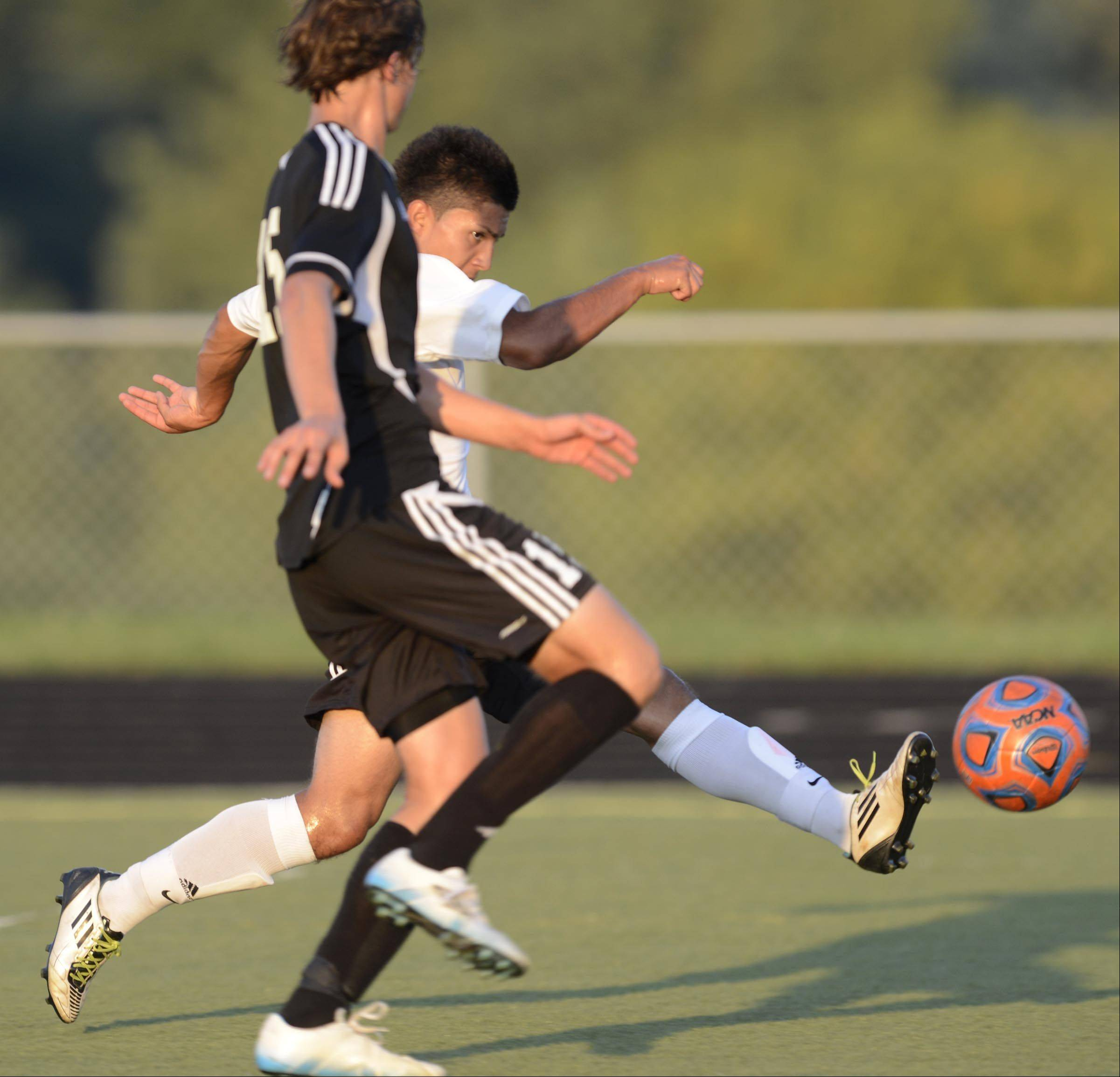 Streamwood's Julio Luna kicks the second goal of the game against Kaneland's Chris Van Dinther Monday in Streamwood.