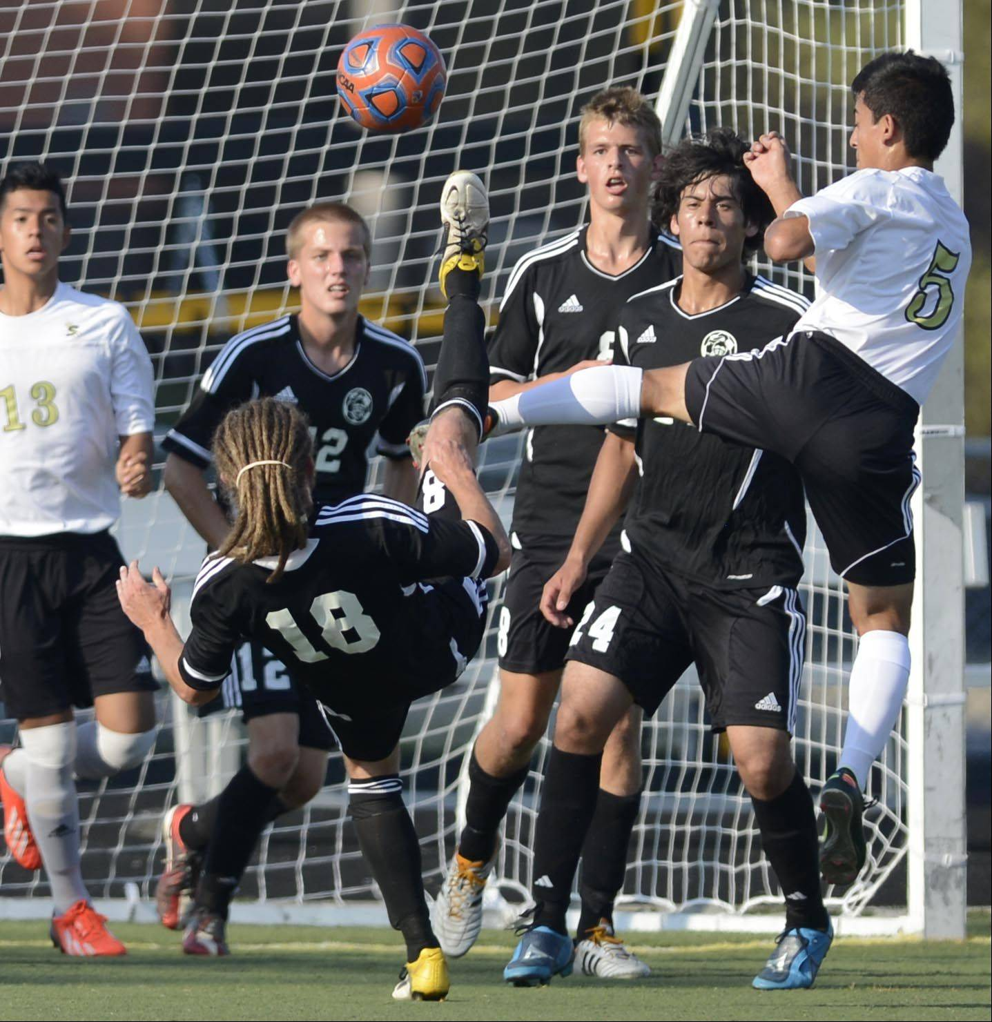 Kaneland's Matt Vander Sande bicycle kicks the ball away from his own goal as Streamwood's Juan Munoz tries to stop him Monday in Streamwood.