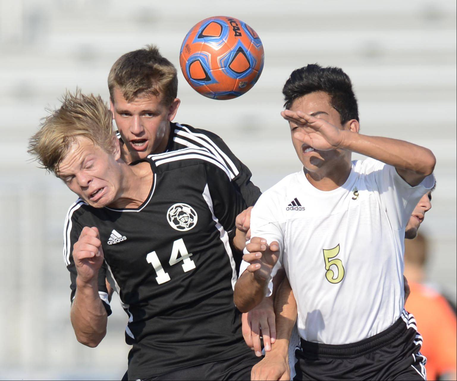 Streamwood's Juan Munoz and Kaneland's Kyle Romas and Kolin Limbrick collide competing for a header Monday in Streamwood.