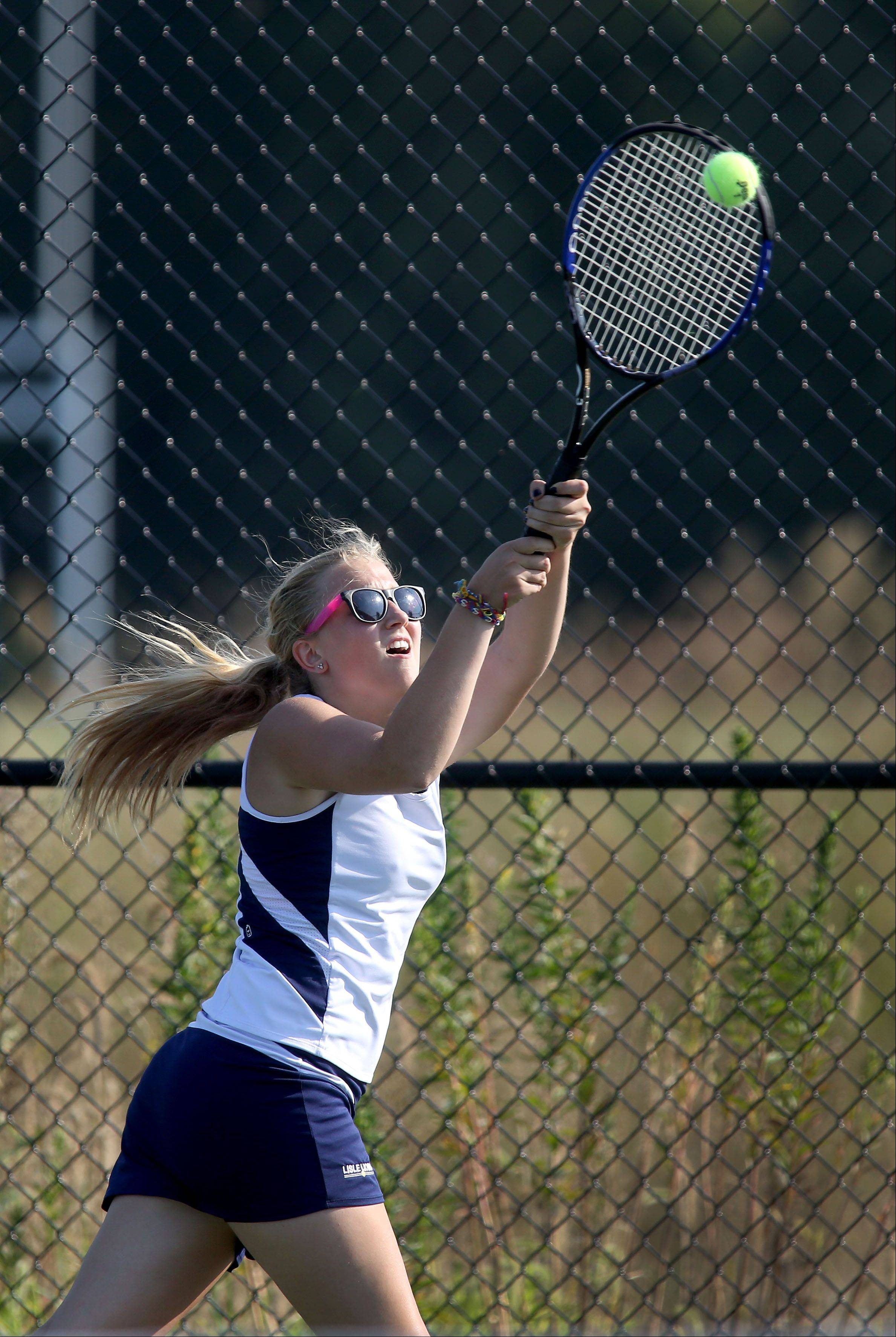 Goda Inokaityte of Lisle reaches up for a return in girls tennis action against Montini on Monday in Lisle.