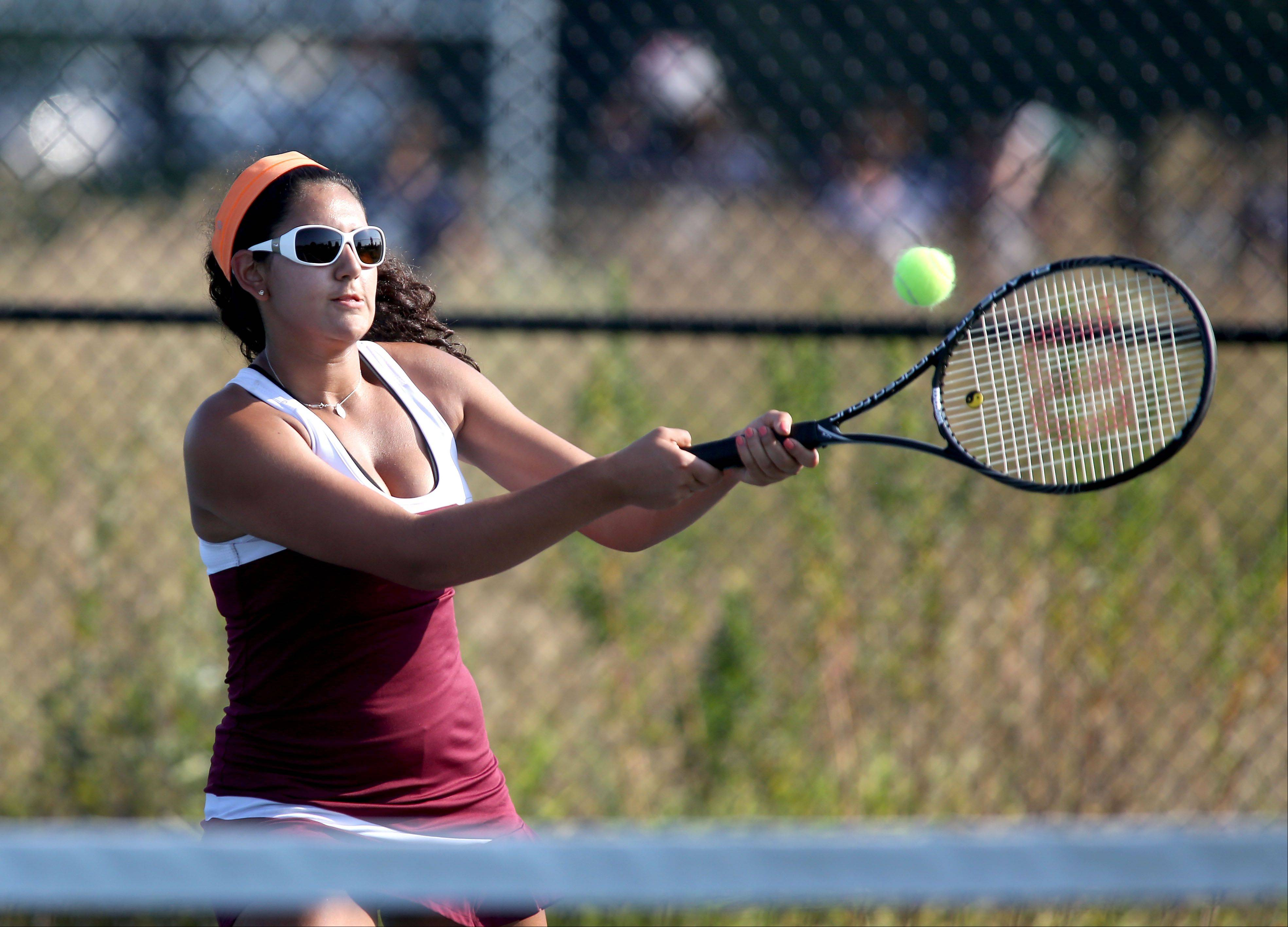 Sofia Yunez of Montini makes a return in action against Lisle during girls tennis on Monday.