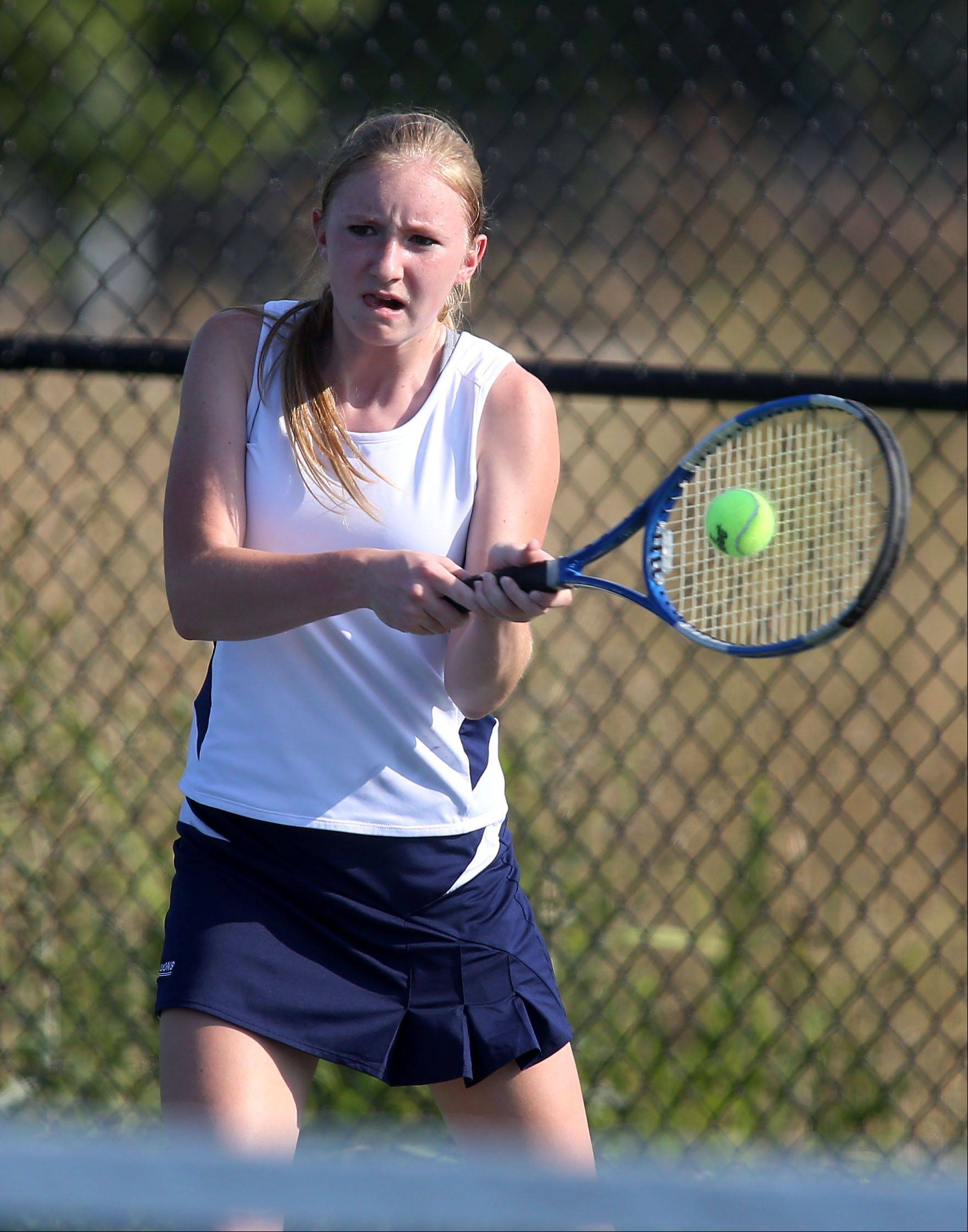 Sarah Mogensen of Lisle returns a shot to Montini in girls tennis action on Monday in Lisle.