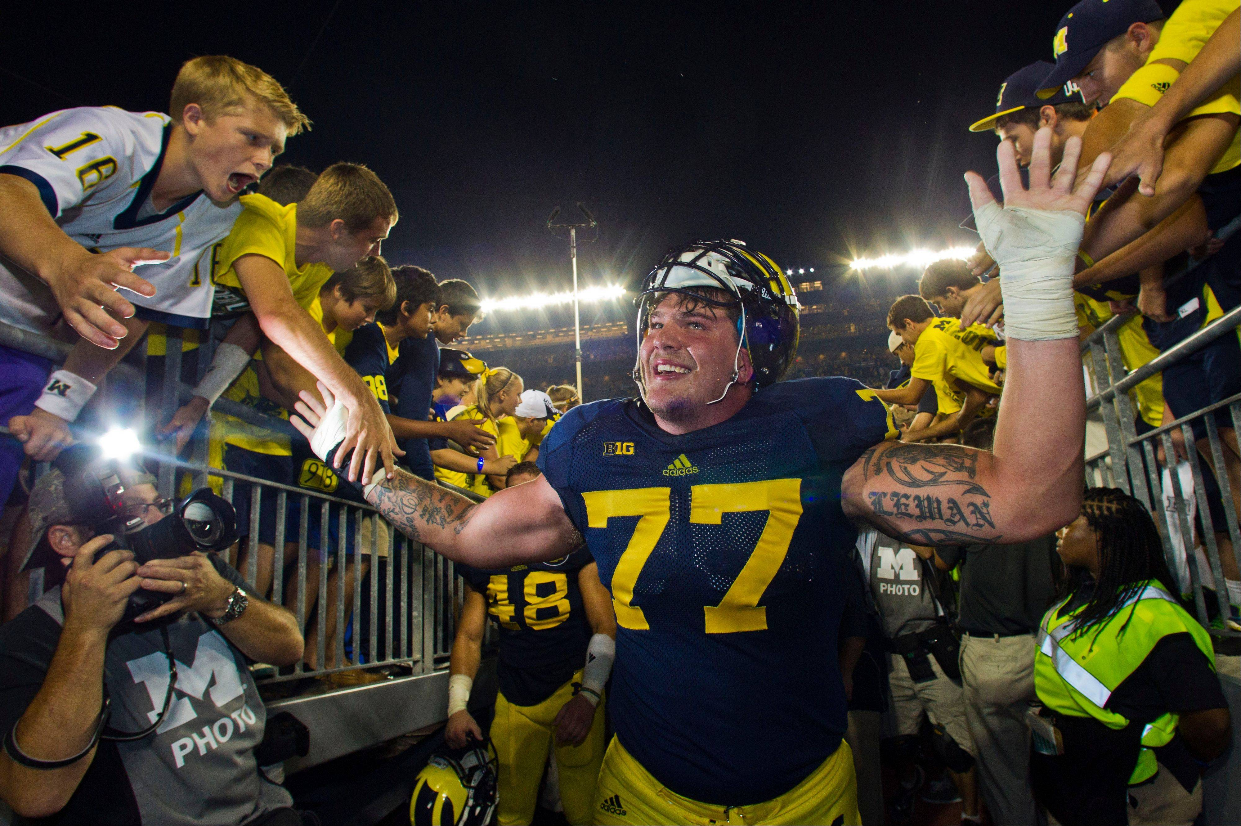 Michigan offensive lineman Taylor Lewan, with tears in his eyes, gives high fives to young fans after a win over Notre Dame on Saturday in Ann Arbor, Mich.