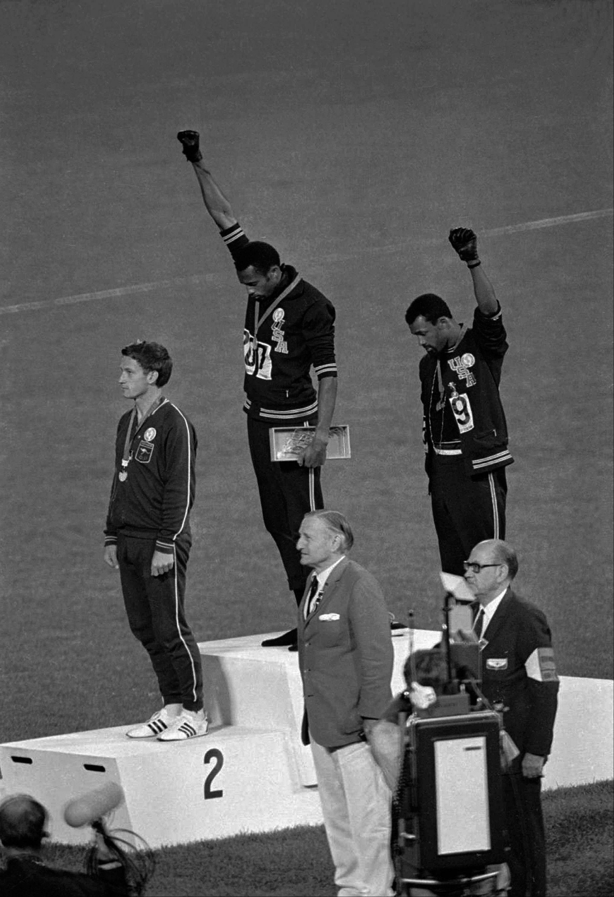"U.S. sprinters Tommie Smith, top center, and John Carlos, top right, extend their gloved fists during the playing of ""The Star-Spangled Banner"" on the medal podium during the 1968 Summer Olympic Games in Mexico City."